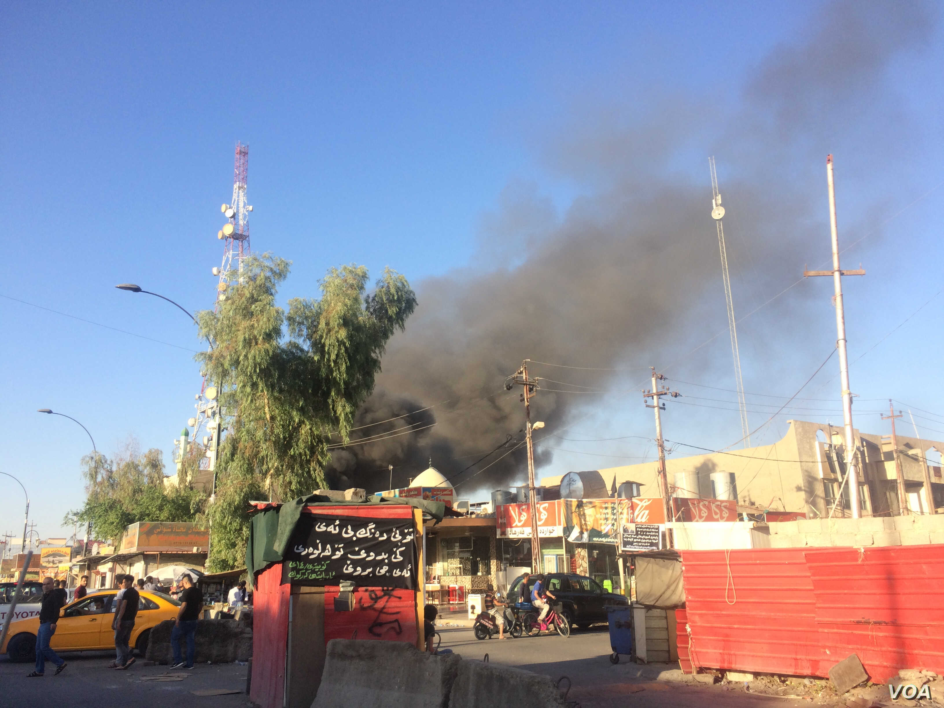 A blaze in a Kurdistan political party office in Kirkuk, Iraq draws onlookers who video the scene on their mobile phones on Oct. 17, 2017. (H.Murdock/VOA)