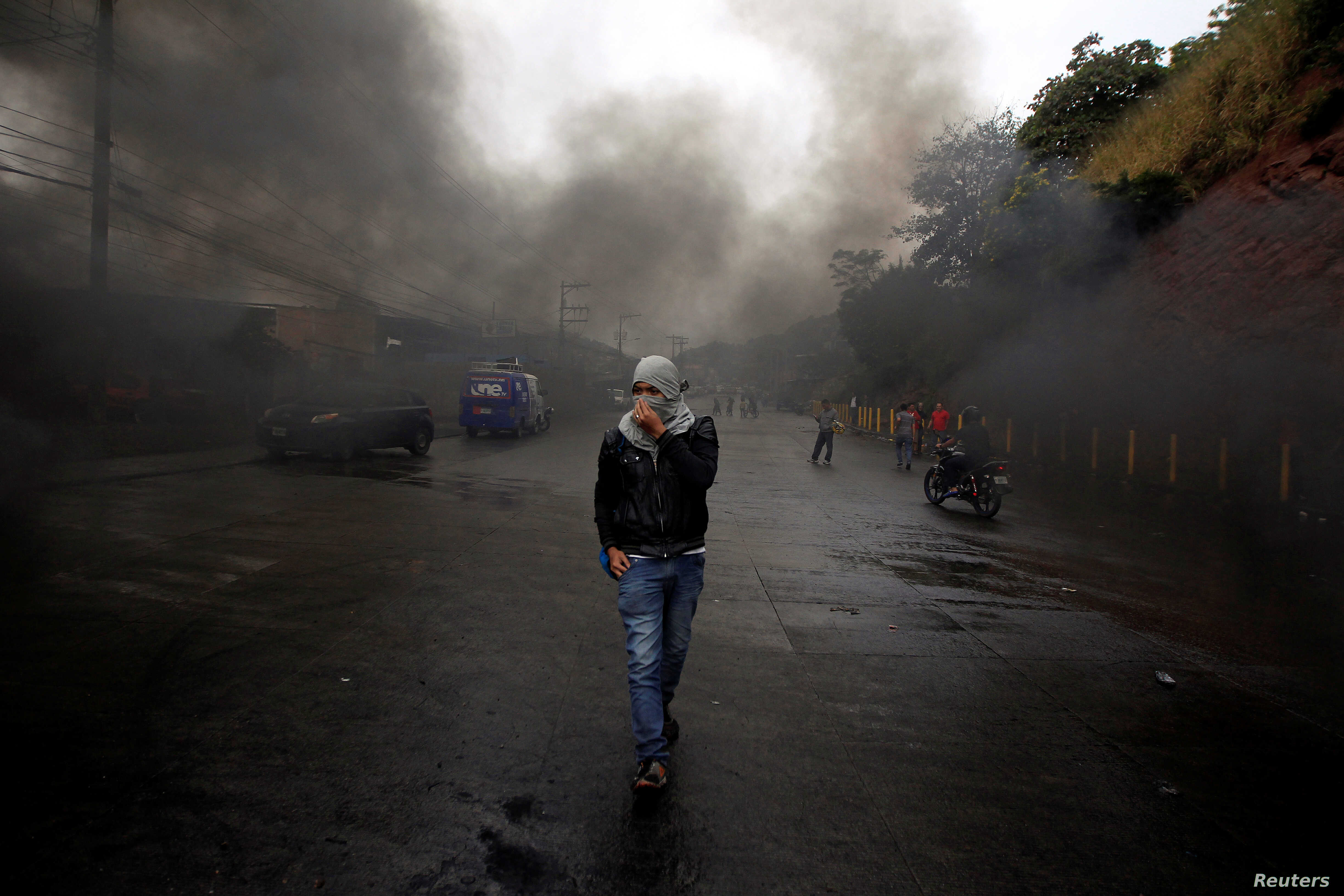 An opposition supporter walks amid smoke during clashes with police after the Organization of American States rejected a declaration of victory for Honduran President Juan Orlando Hernandez in a sharply disputed election, in Tegucigalpa, Dec. 18, 201...