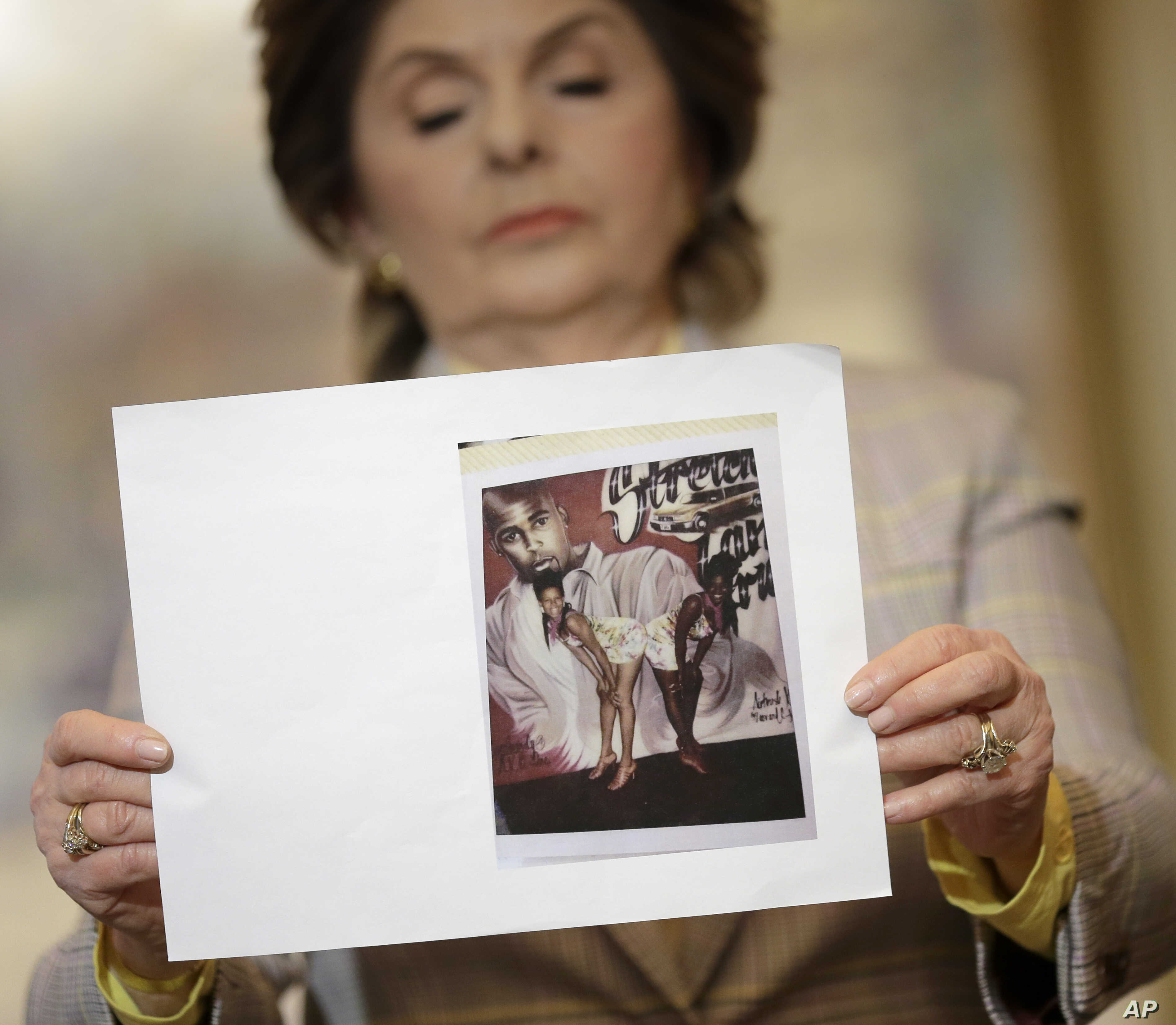 During a news conference  in New York, Feb. 21, 2019, attorney Gloria Allred holds up a picture of Latresa Scaff, left, and Rochelle Washington, posing in front of a picture of R. Kelly, on the night they say they became victims of his sexual advance...