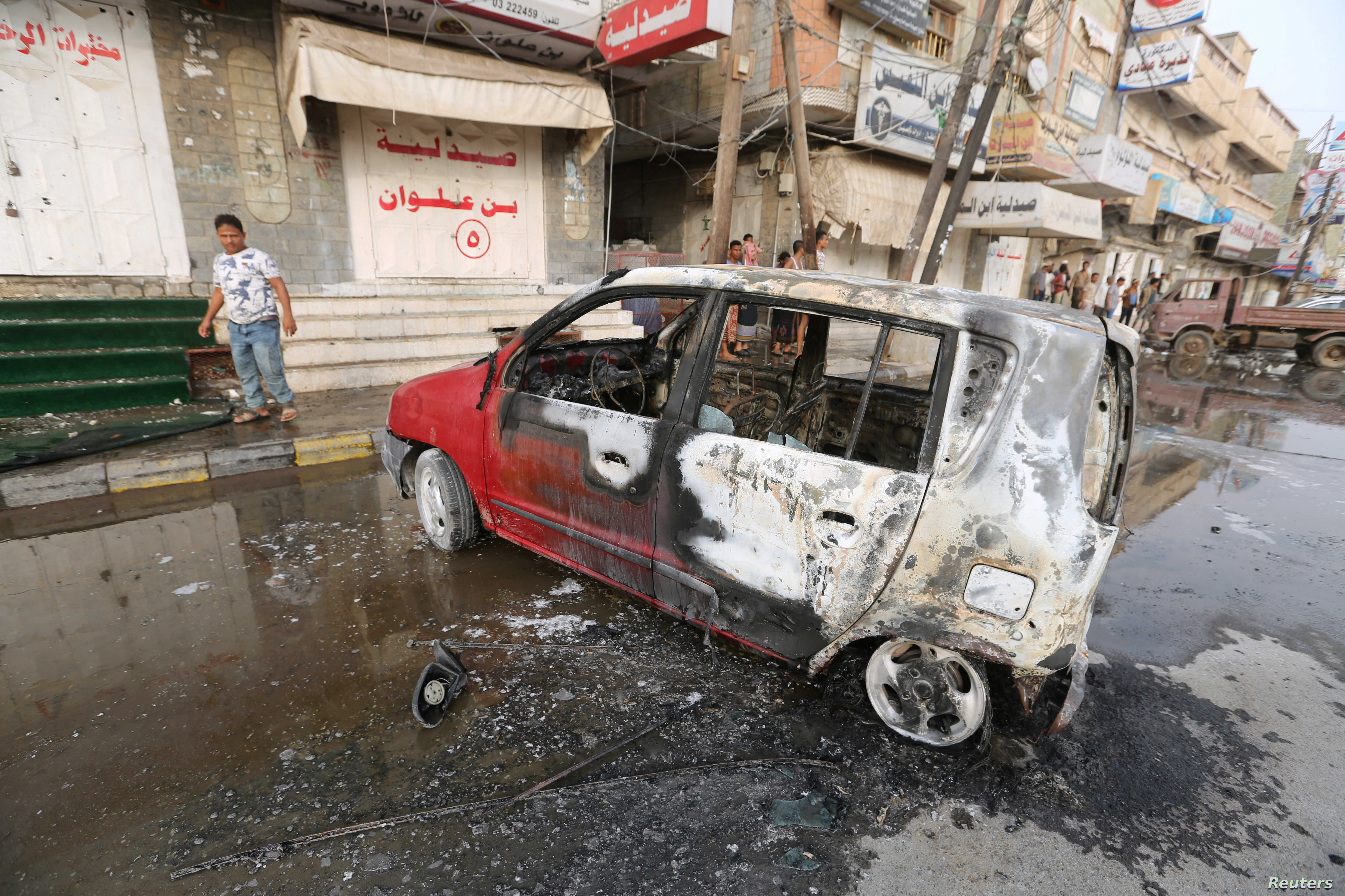FILE - A man stands by a car damaged by a strike near al-Thawra Hospital in Hodeidah, Yemen, Aug. 2, 2018.