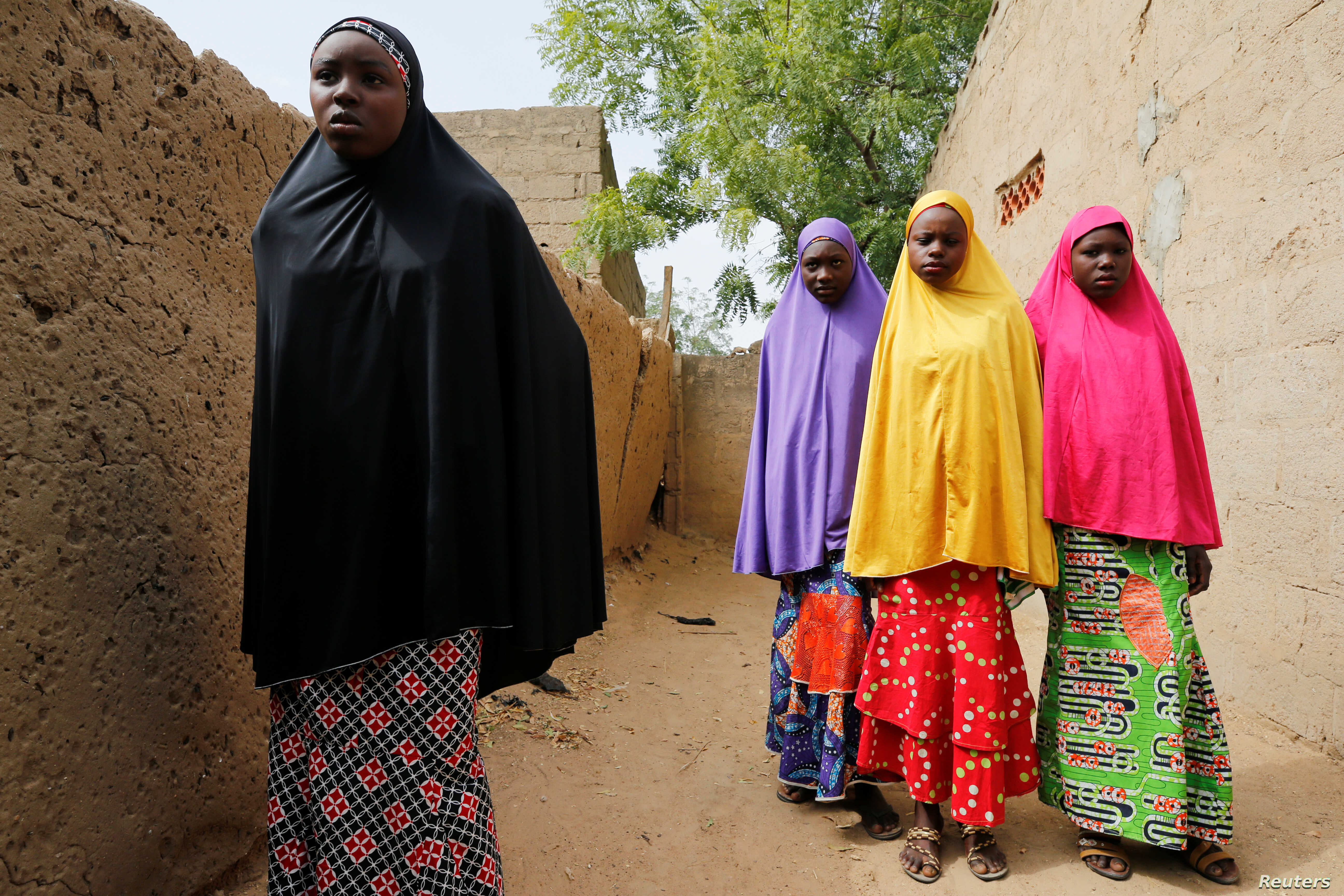 Amina Usman (L), a 15-year-old student, who was among those who escaped the attack on her school, stands with her sisters in Dapchi, Nigeria, Feb. 23, 2018.