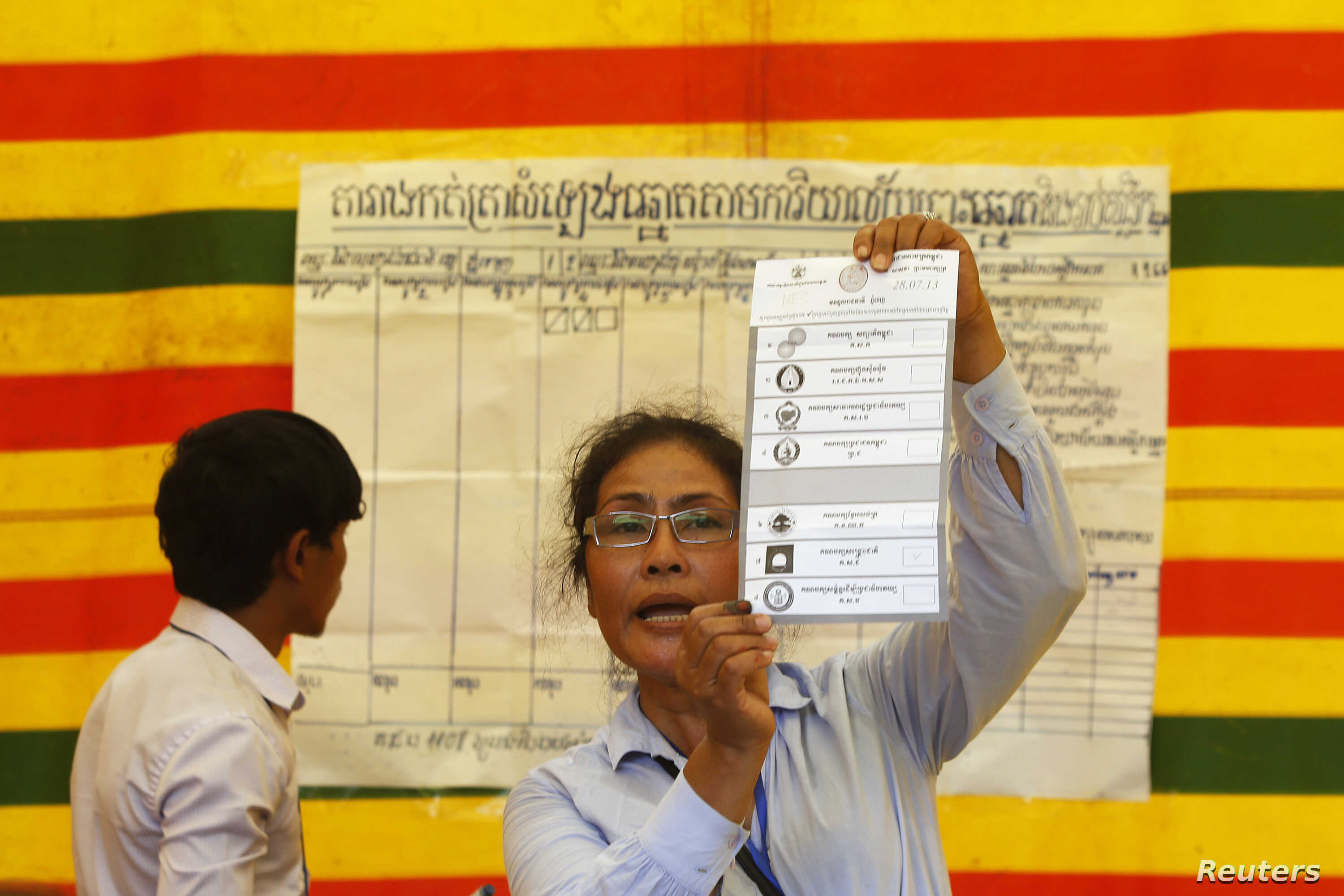 FILE - An election official shows a ballot paper as votes are counted at a polling station in Phnom Penh, July 28, 2013.