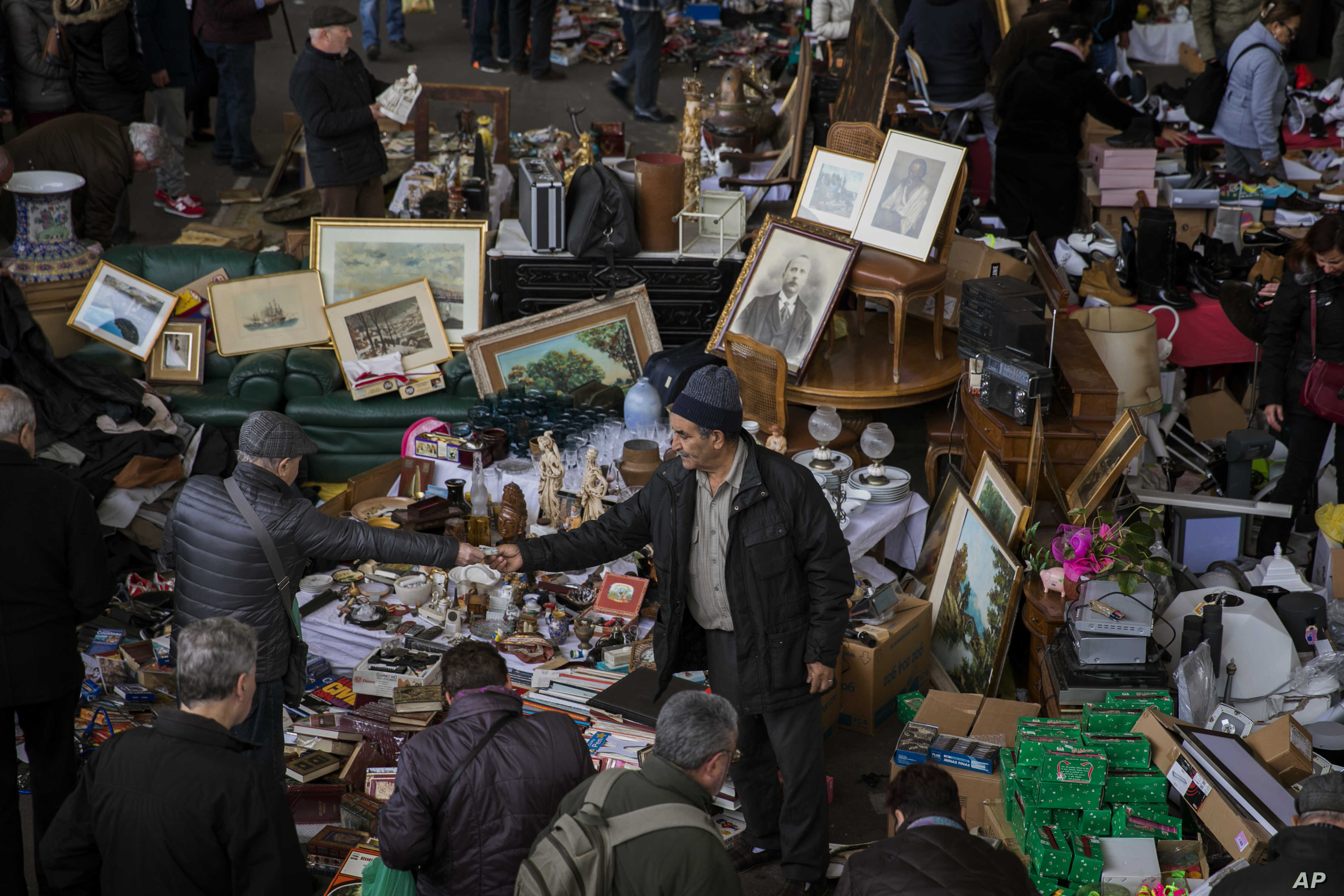 People buy items at a stall street in Barcelona, Spain, Monday, Dec. 18, 2017. Jittery businessmen in Catalonia have put their investment plans on ice as they brace for the region's parliamentary election on Thursday, Dec. 21, 2017.
