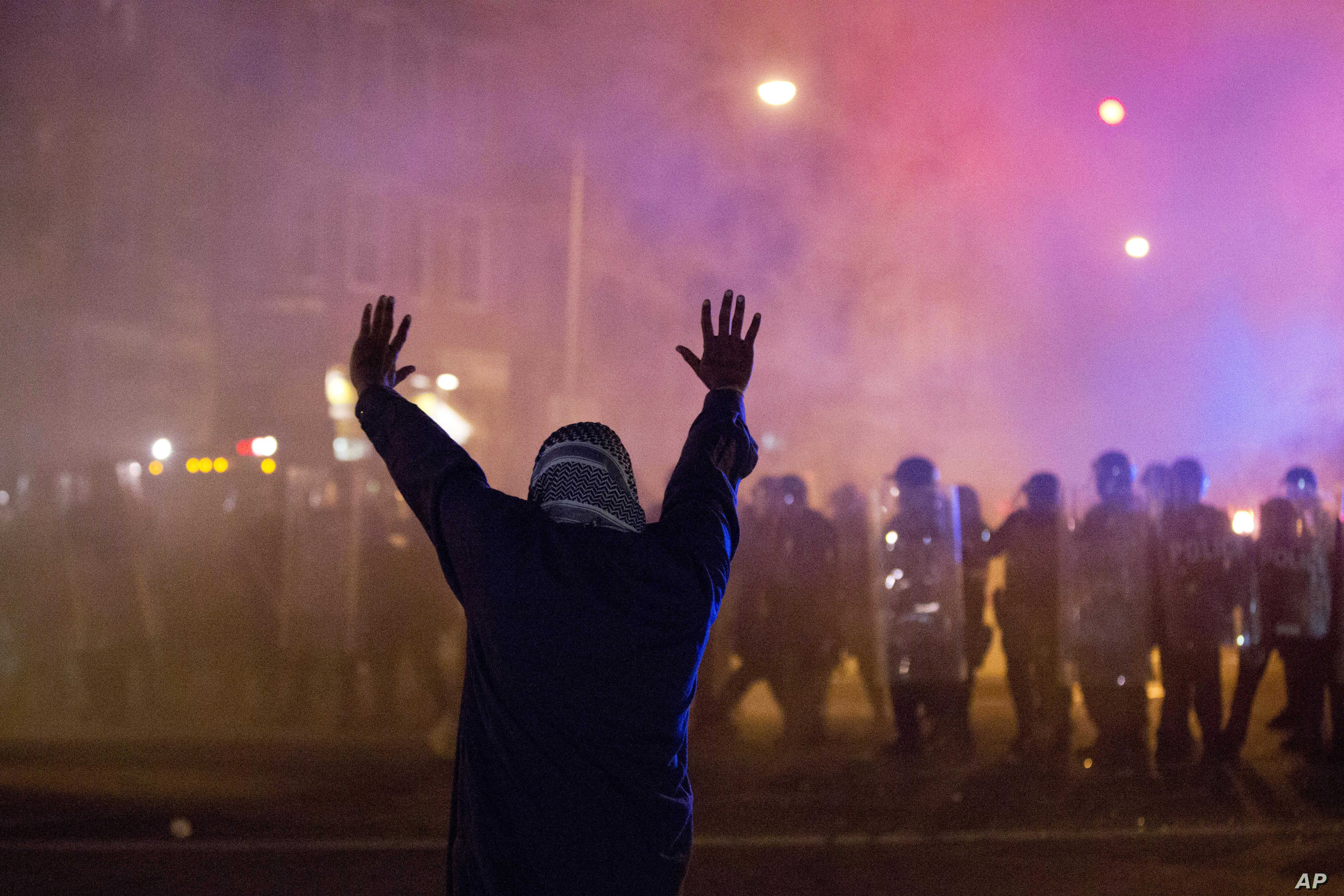 A protestor faces police enforcing a curfew April 28, 2015, in Baltimore. A line of police behind riot shields hurled smoke grenades and fired pepper balls at dozens of protesters to enforce a citywide curfew.
