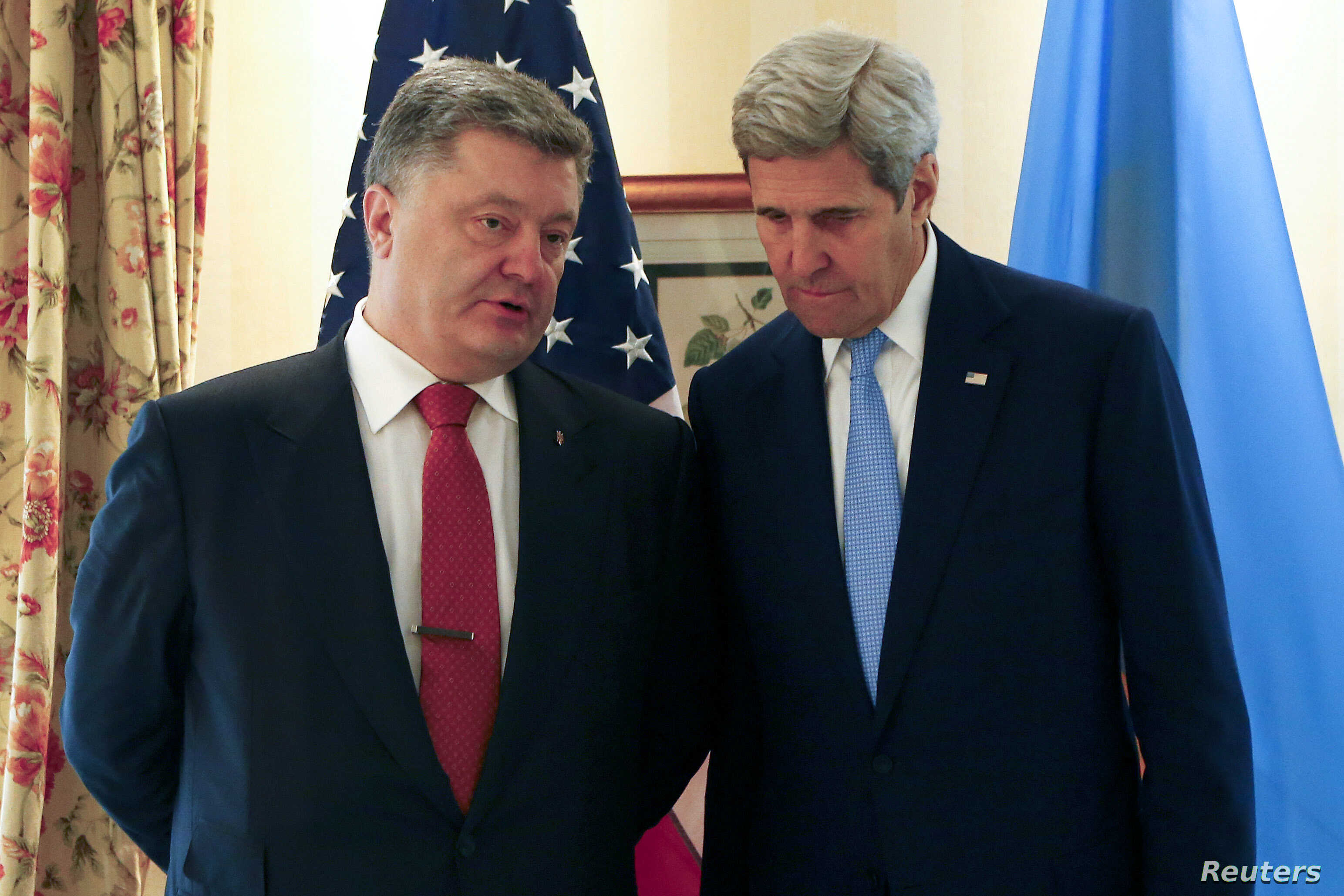 U.S. Secretary of State John Kerry (R) listens to Ukrainian President Petro Poroshenko before their meeting at the Munich Security Conference in Munich, Germany, Feb. 13, 2016.