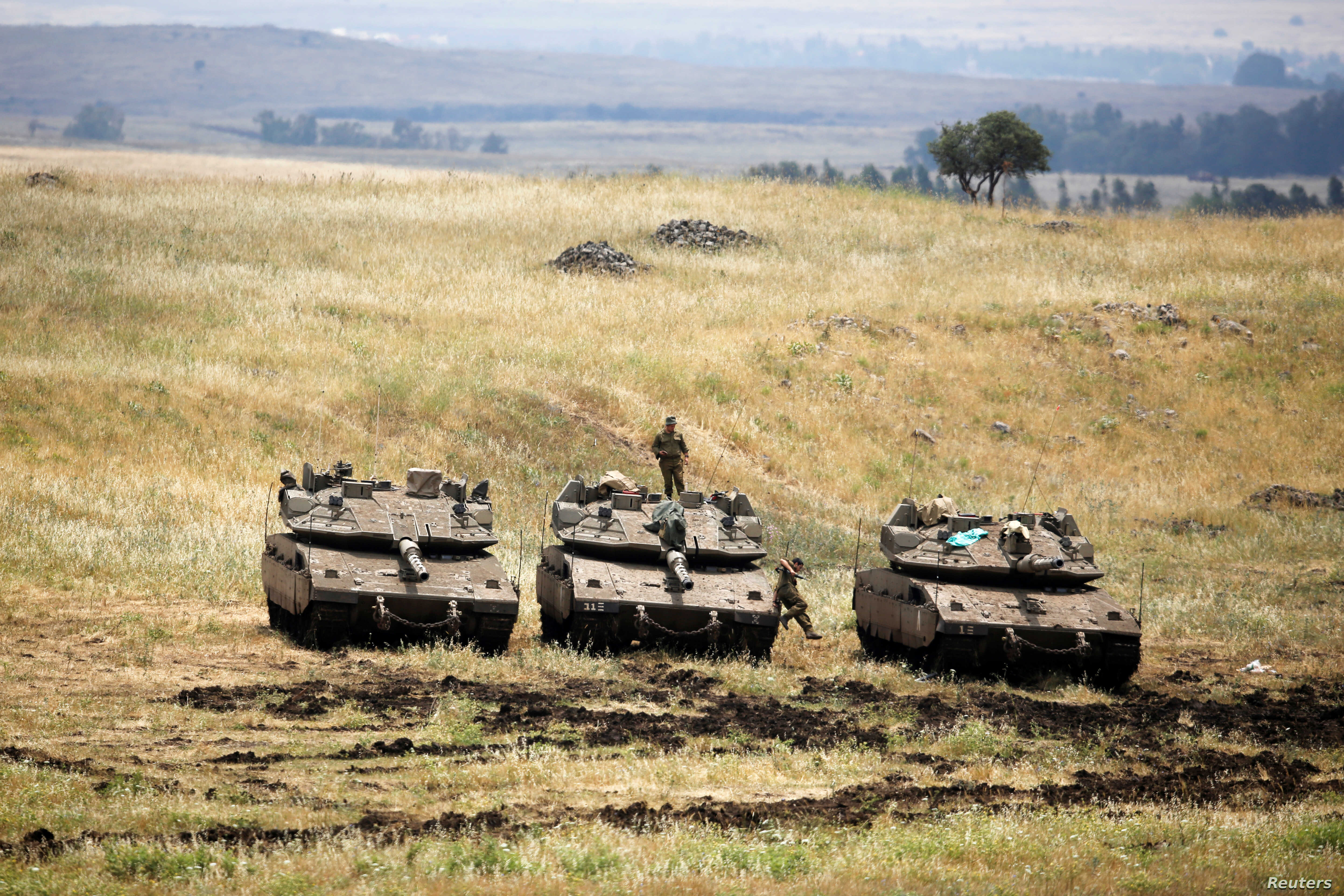 An Israeli soldier stands on a tank as another jumps off it near the Israeli side of the border with Syria in the Israeli-occupied Golan Heights, Israel, May 9, 2018.