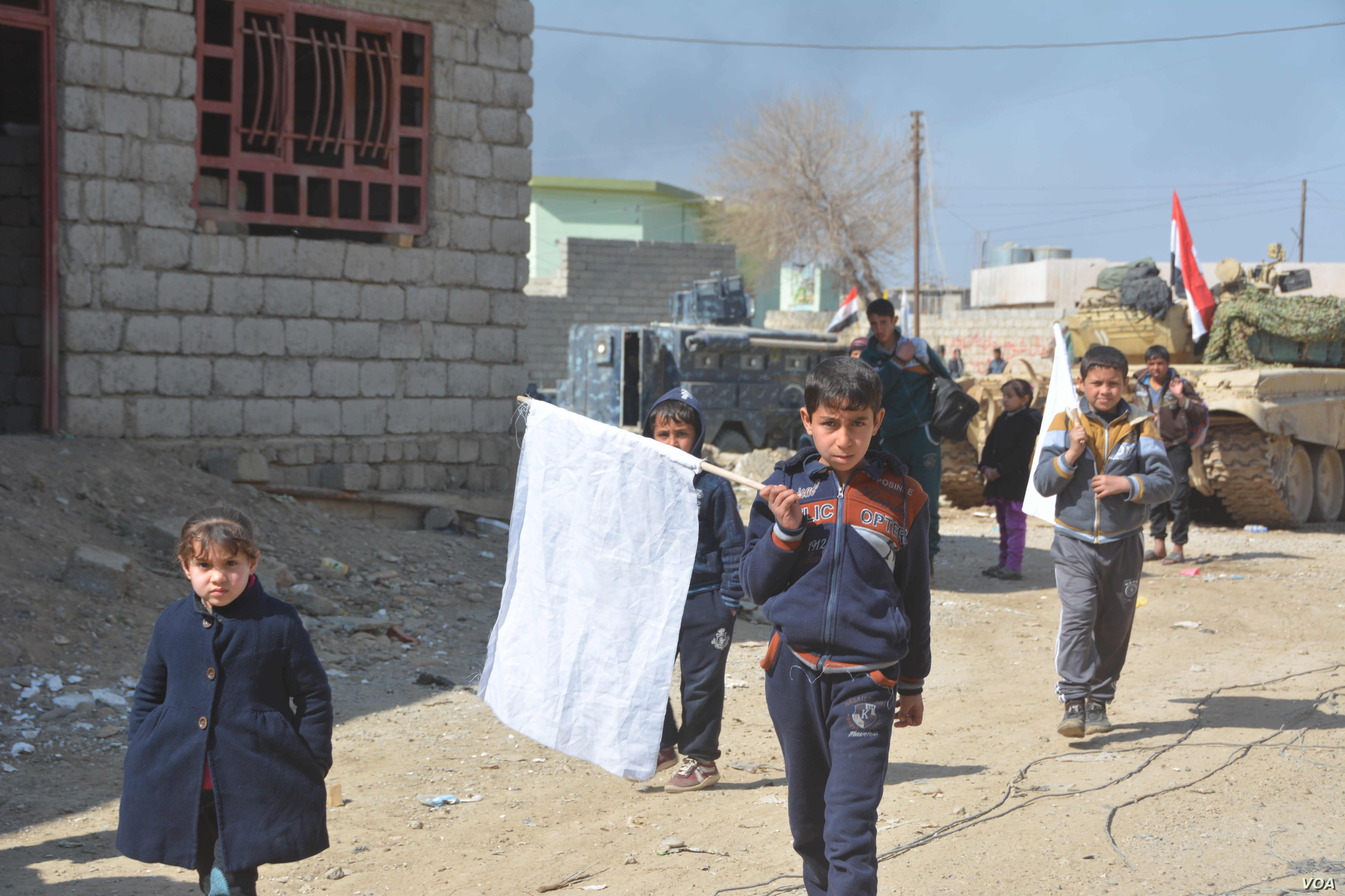 Children carry white flags as they flee IS and disputed neighborhoods, hoping to encourage all sides to hold their fire in the al-Josaq suburb of Mosul, Iraq, Feb. 26, 2017. (Mahmood Alsalih/VOA)