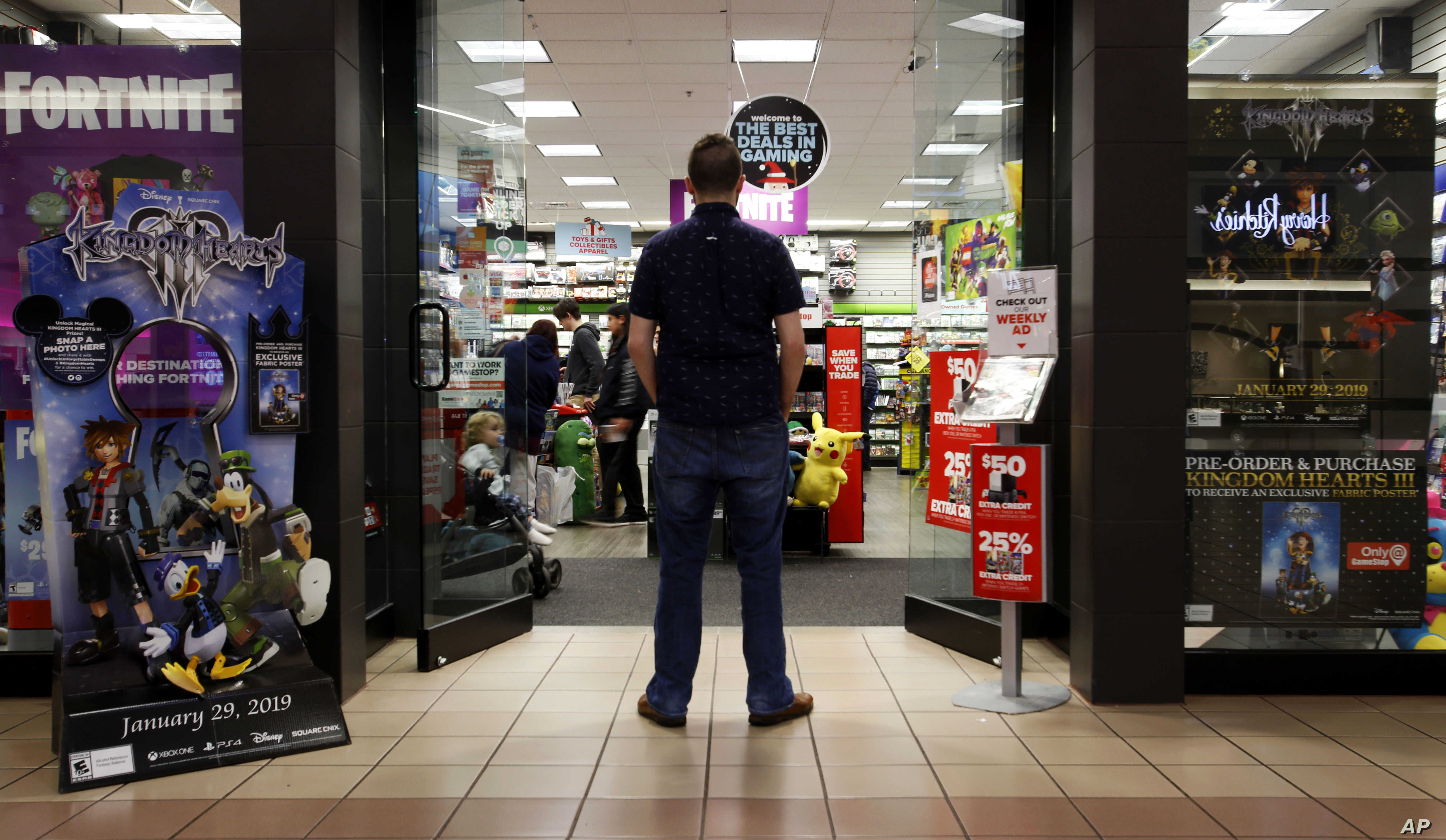 FILE - A 27-year-old self-described tech addict poses for a portrait in front of a video game store at a mall in Everett, Wash., Dec. 9, 2018.