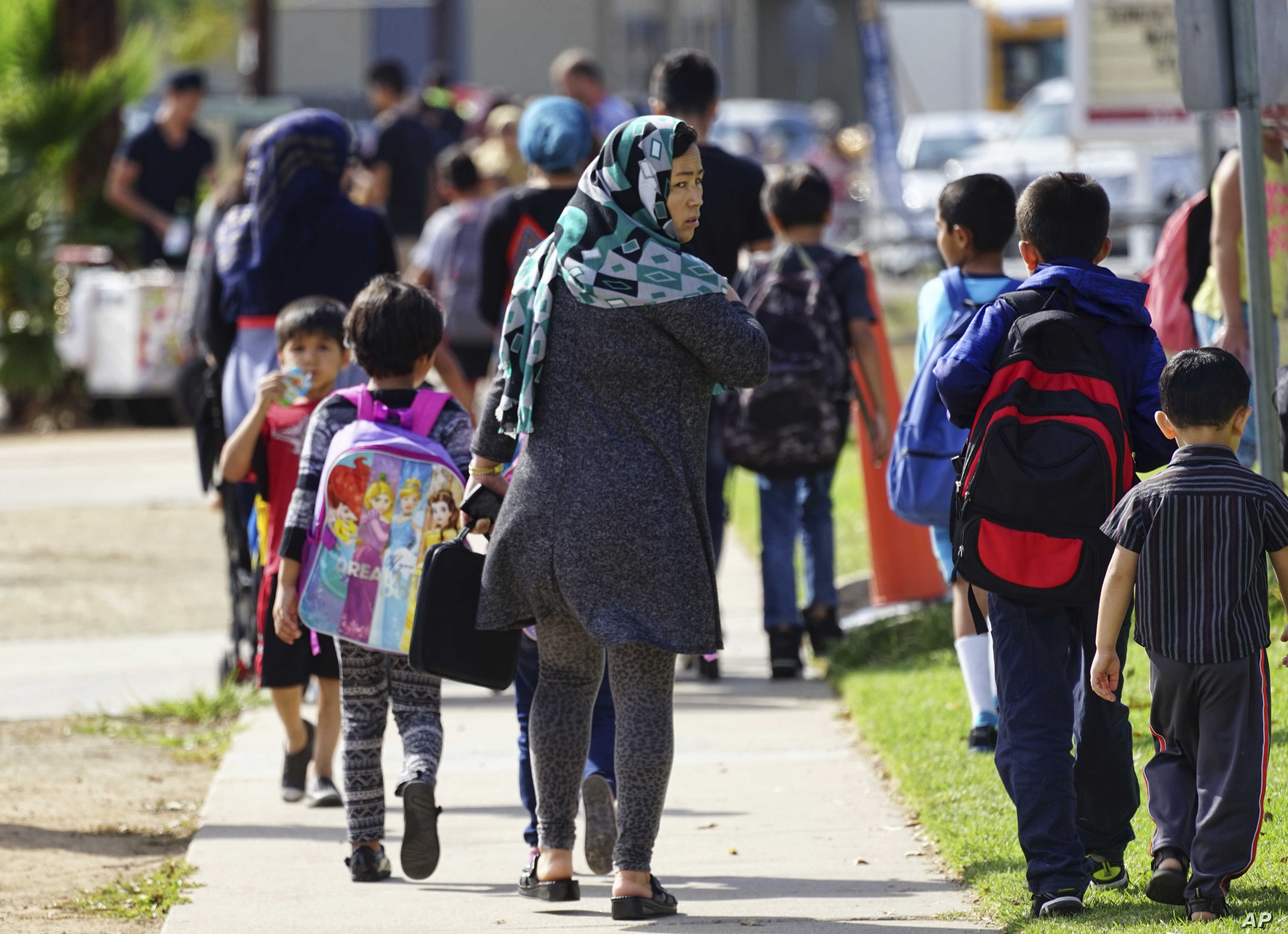 FILE - In this Oct. 5, 2016 photo, parents pick up their children at Naranca Elementary in El Cajon, Calif. The school is one of many in the San Diego suburb that has received an influx of Syrian refugees.