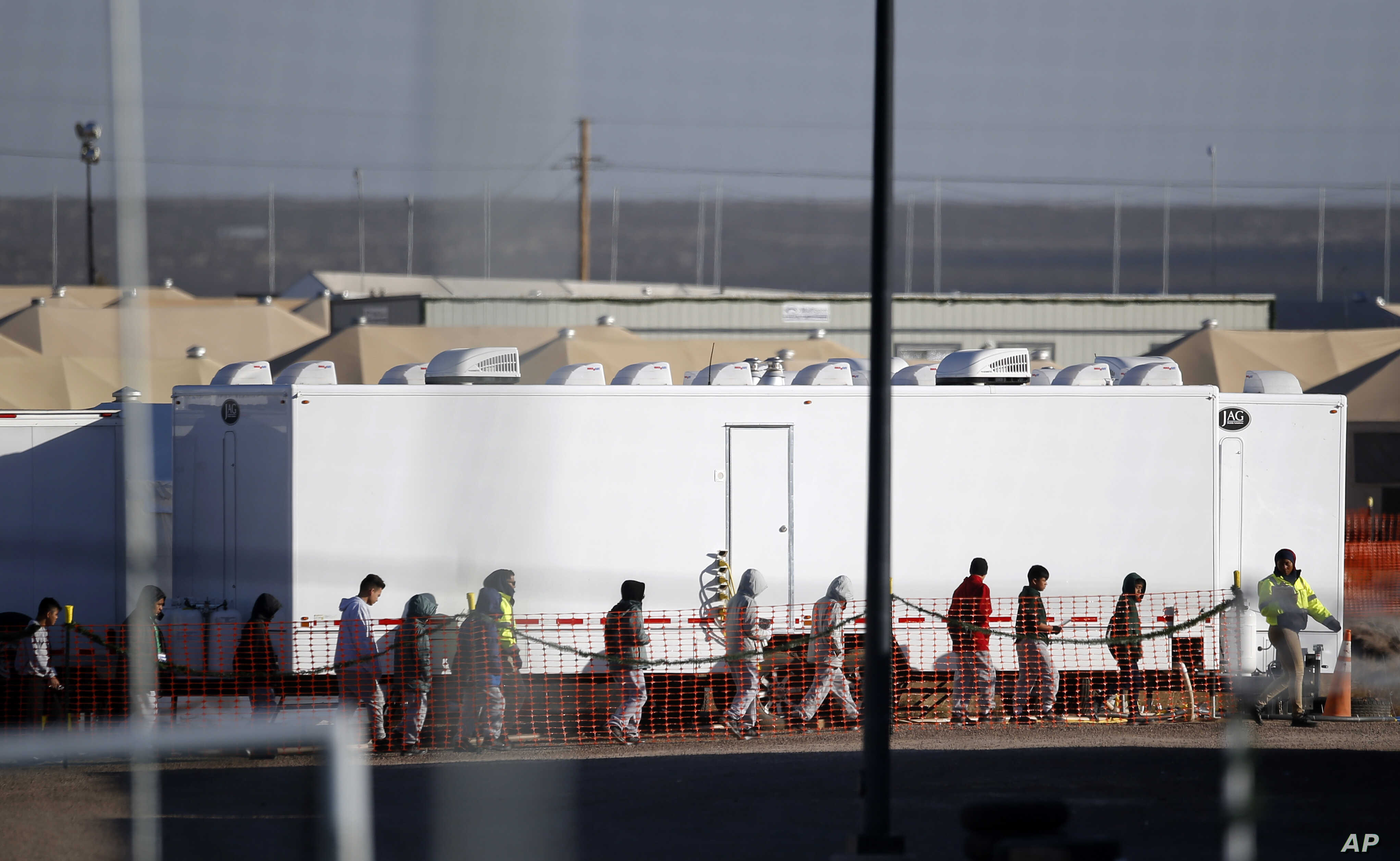 Migrant teens walk in a line through the Tornillo detention camp in Tornillo, Texas, Thursday, Dec. 13, 2018. The Trump administration announced in June 2018 that it would open the temporary shelter for up to 360 migrant children in this isolated cor...