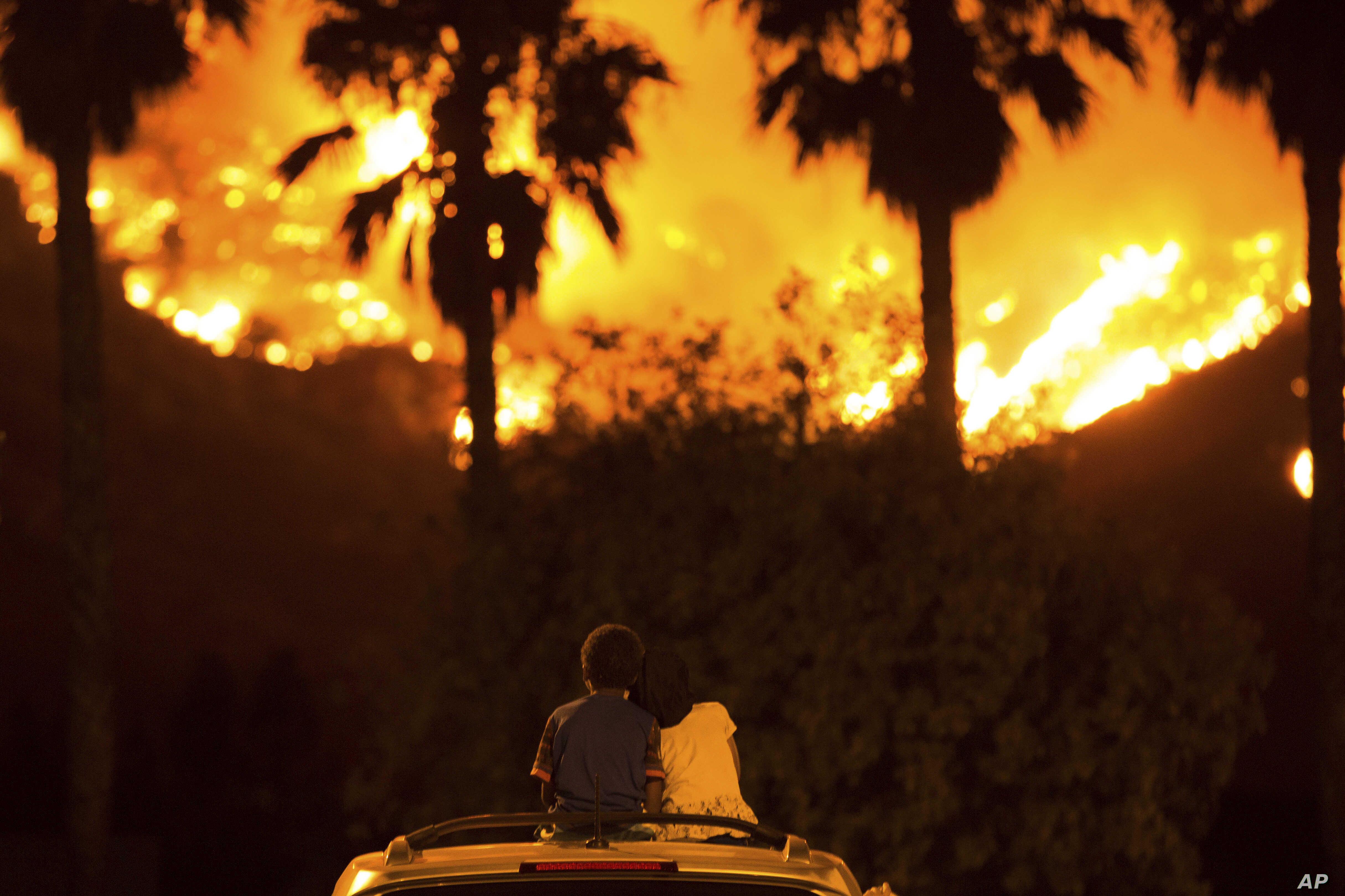King Bass, 6 (L) sits and watches the Holy Fire burn from on top of his parents' car as his sister Princess, 5, rests her head on his shoulder, Aug. 9, 2018 in Lake Elsinore, Calif.