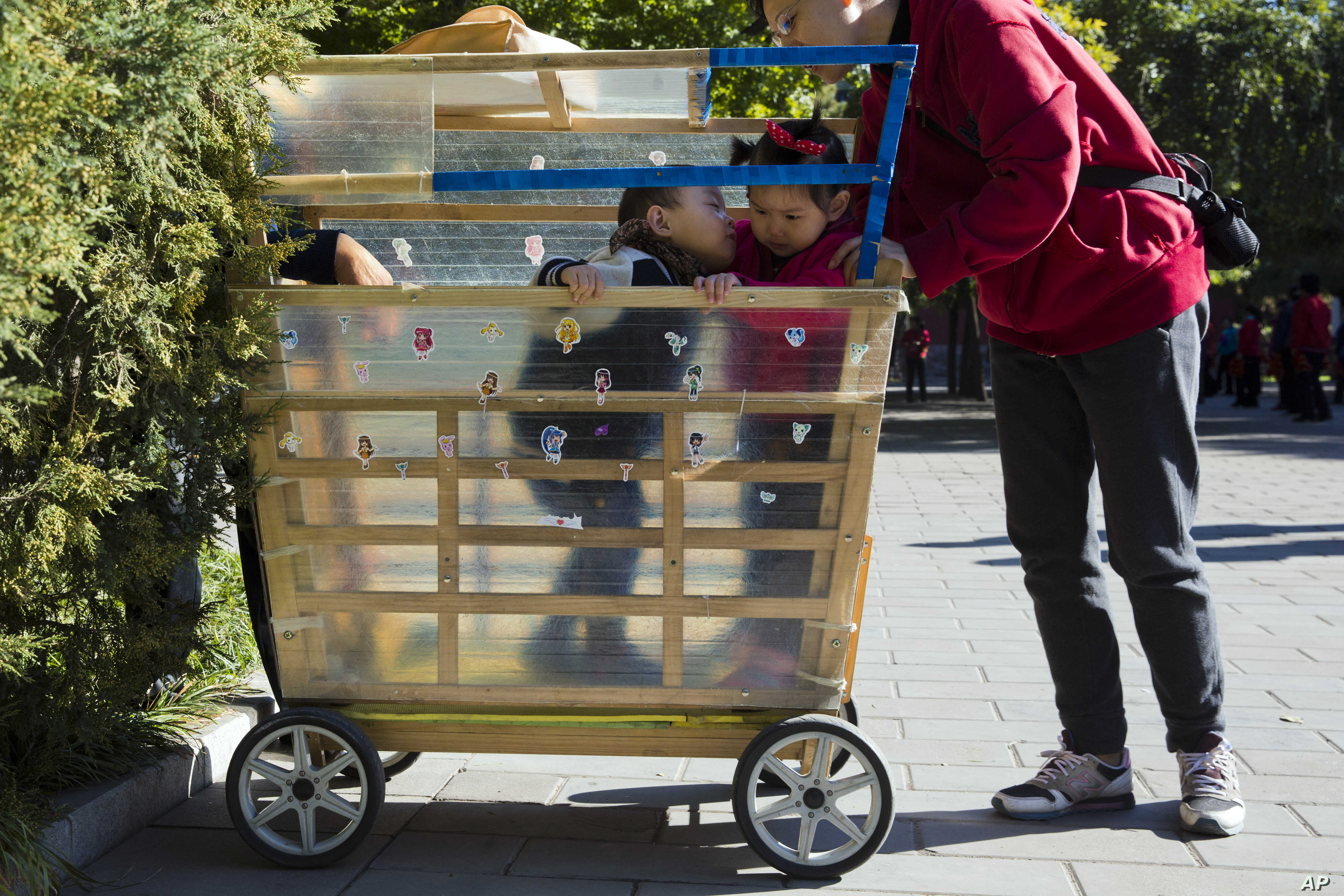 A boy tries to kiss a girl who is placed in his home made stroller in Beijing, China, Oct. 30, 2015.