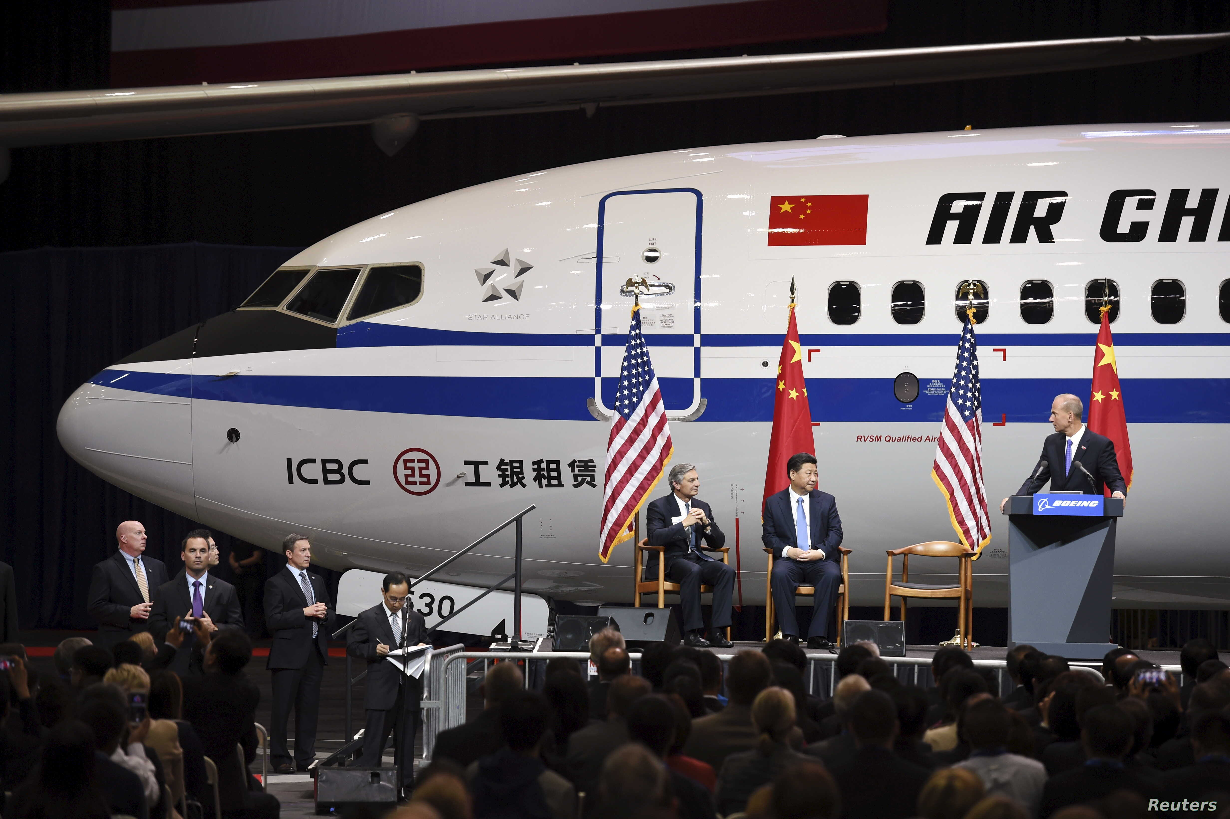 Chinese President Xi Jinping (C) and Ray Conner (L), president of Boeing Commercial Airplanes, watch as Boeing Co Chief Executive Dennis Muilenburg (R) stands at a podium, after Xi's tour of the Boeing assembly line in Everett, Washington September 2...