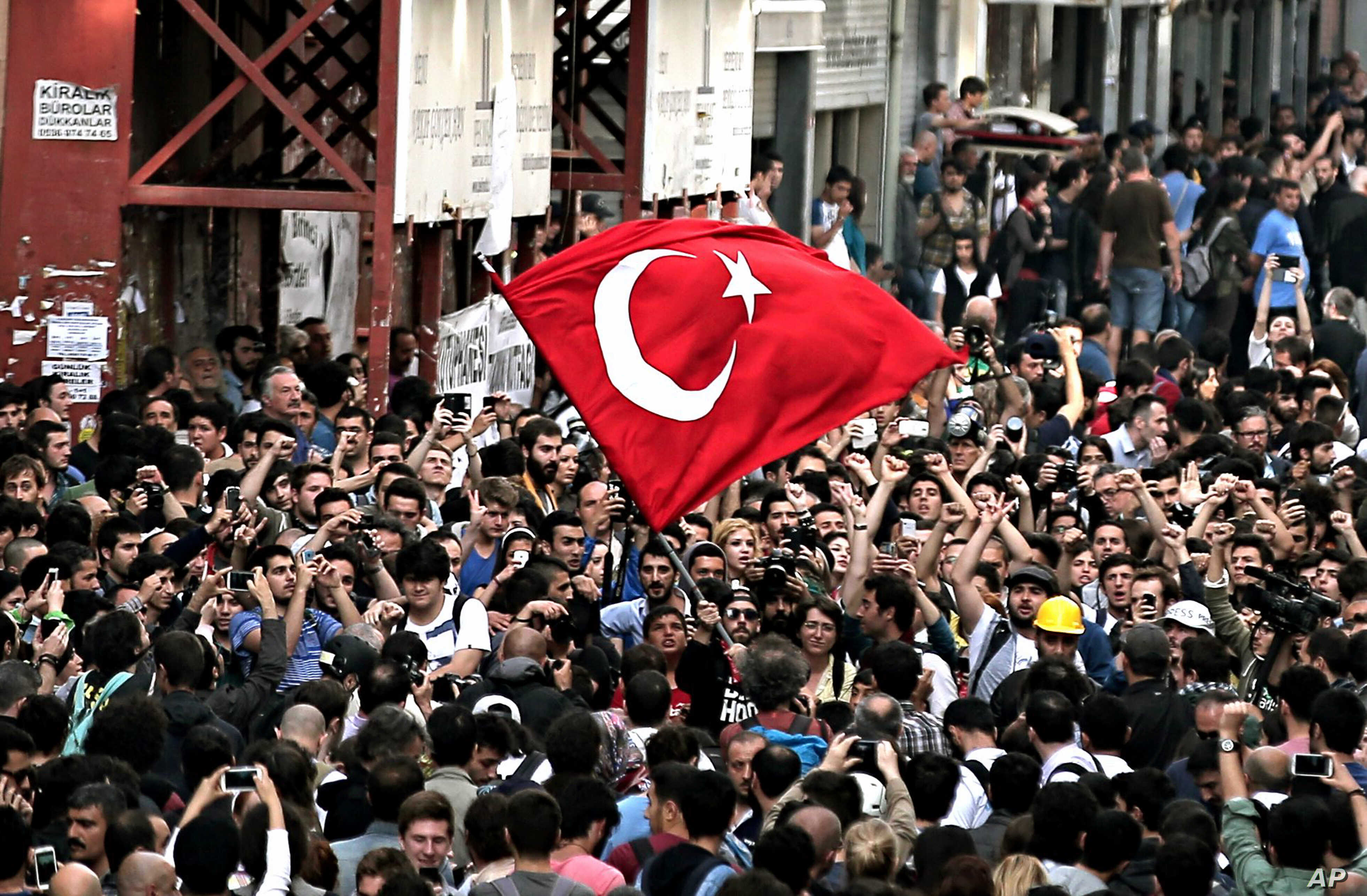 FILE - People try to march after security members closed the city's landmark Taksim Square and Gezi Park, on the first anniversary of the Gezi protests in Istanbul, Turkey, May 31, 2014. A government backed redevelopment plan for Gezi Park in Istanbu...