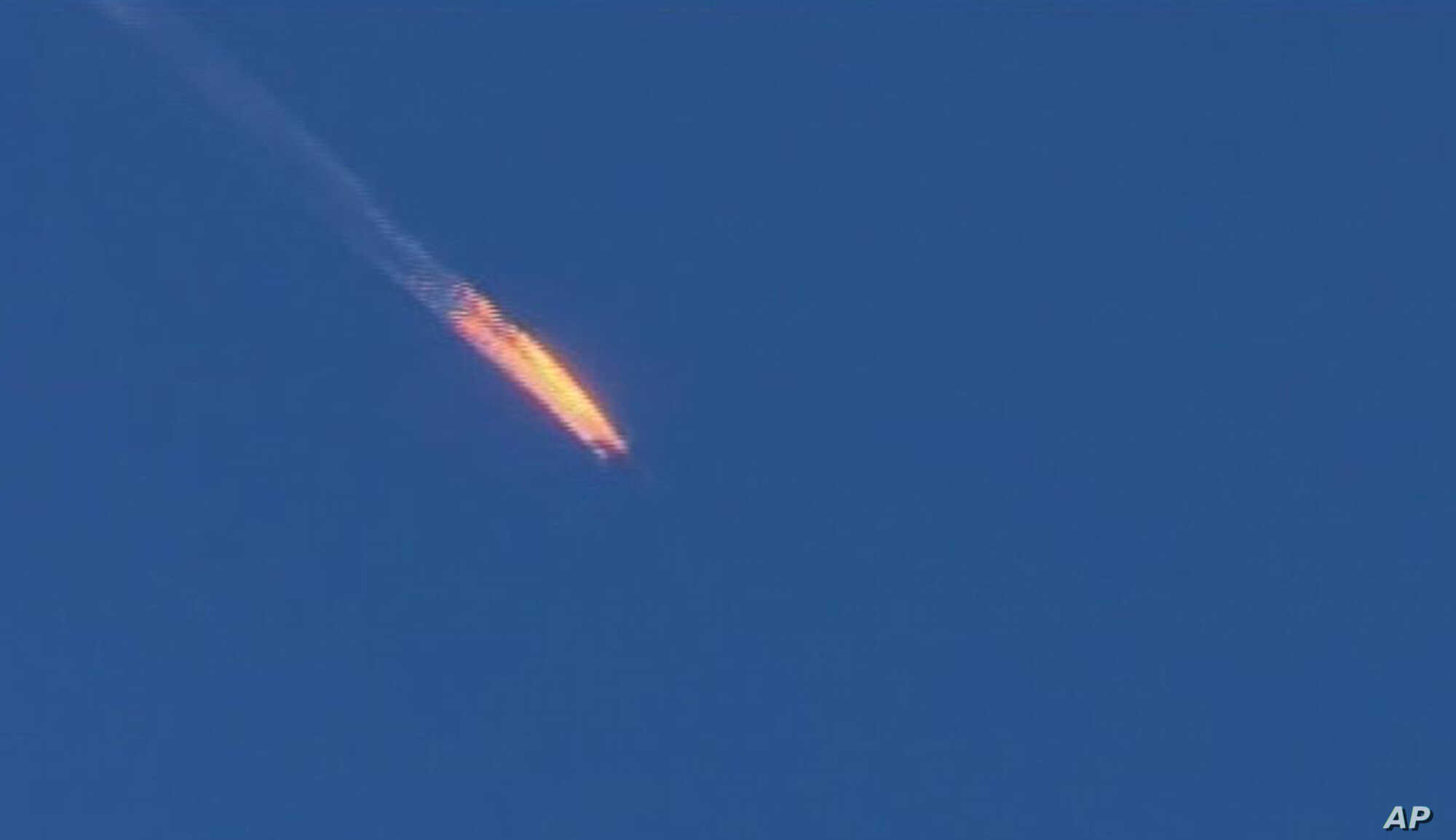 This frame grab from video by Haberturk TV, shows a Russian warplane on fire before crashing on a hill as seen from Hatay province, Turkey, Tuesday, Nov. 24, 2015.