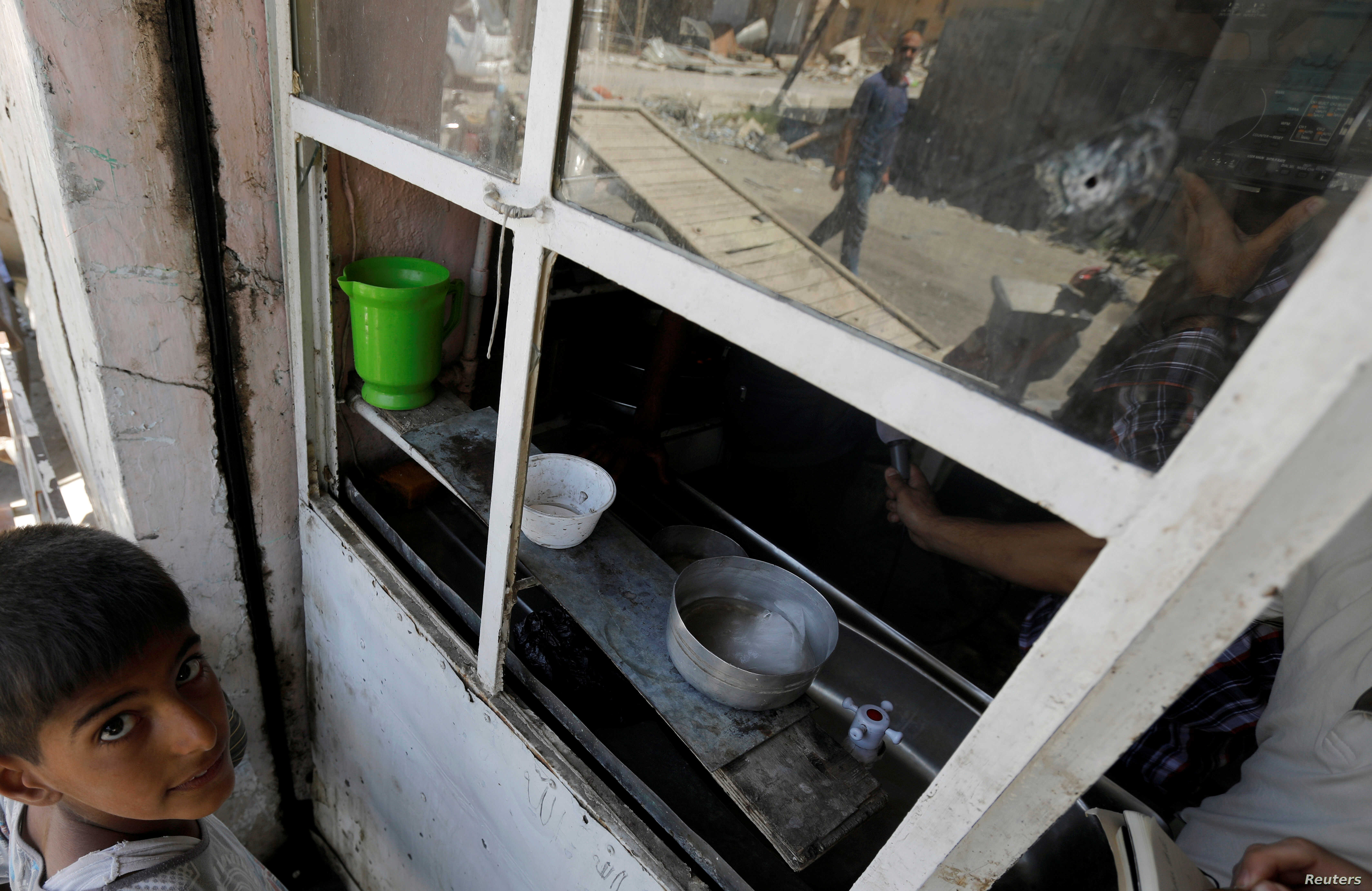 An Iraqi man is seen reflected in a cafe window in the destroyed Old City of Mosul, Iraq, Aug. 7, 2017.