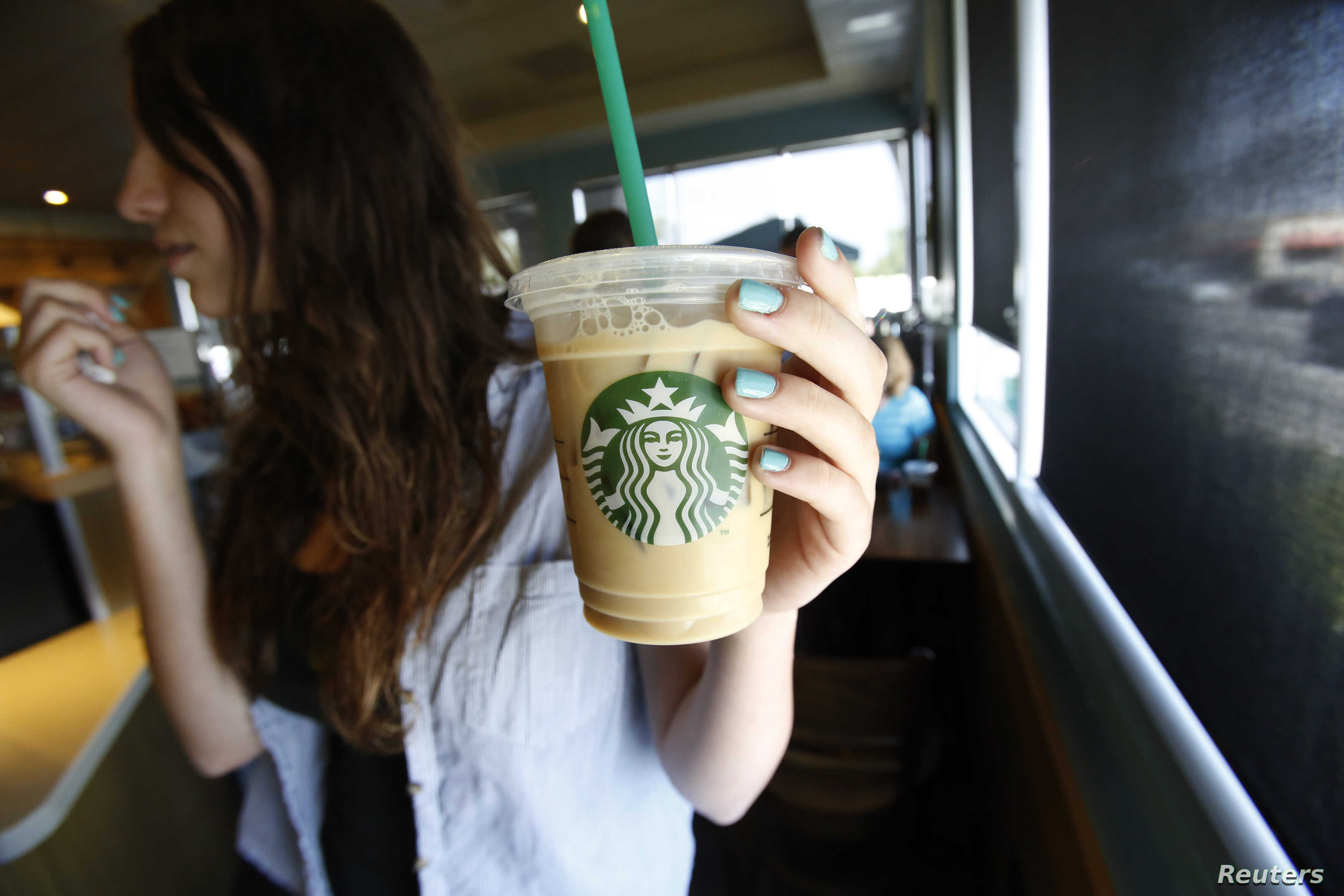 A patron holds an iced beverage at a Starbucks coffee store in Pasadena, Calif., July 25, 2013. Straws and stirrers are among the top 10 items found in coastal trash cleanups.
