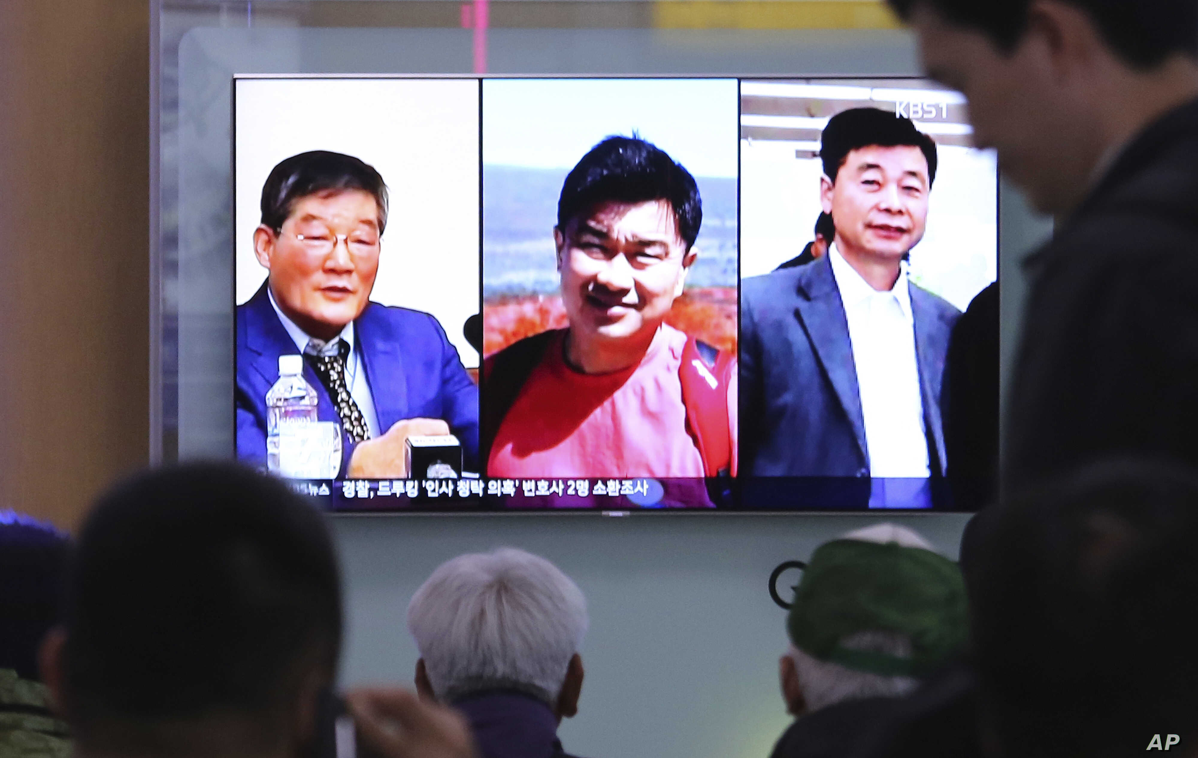 People watch a TV news report on screen, showing portraits of three Americans, Kim Dong Chul (L), Tony Kim, and Kim Hak Song (R) detained in the North Korea at the Seoul Railway Station in Seoul, South Korea, May 3, 2018.
