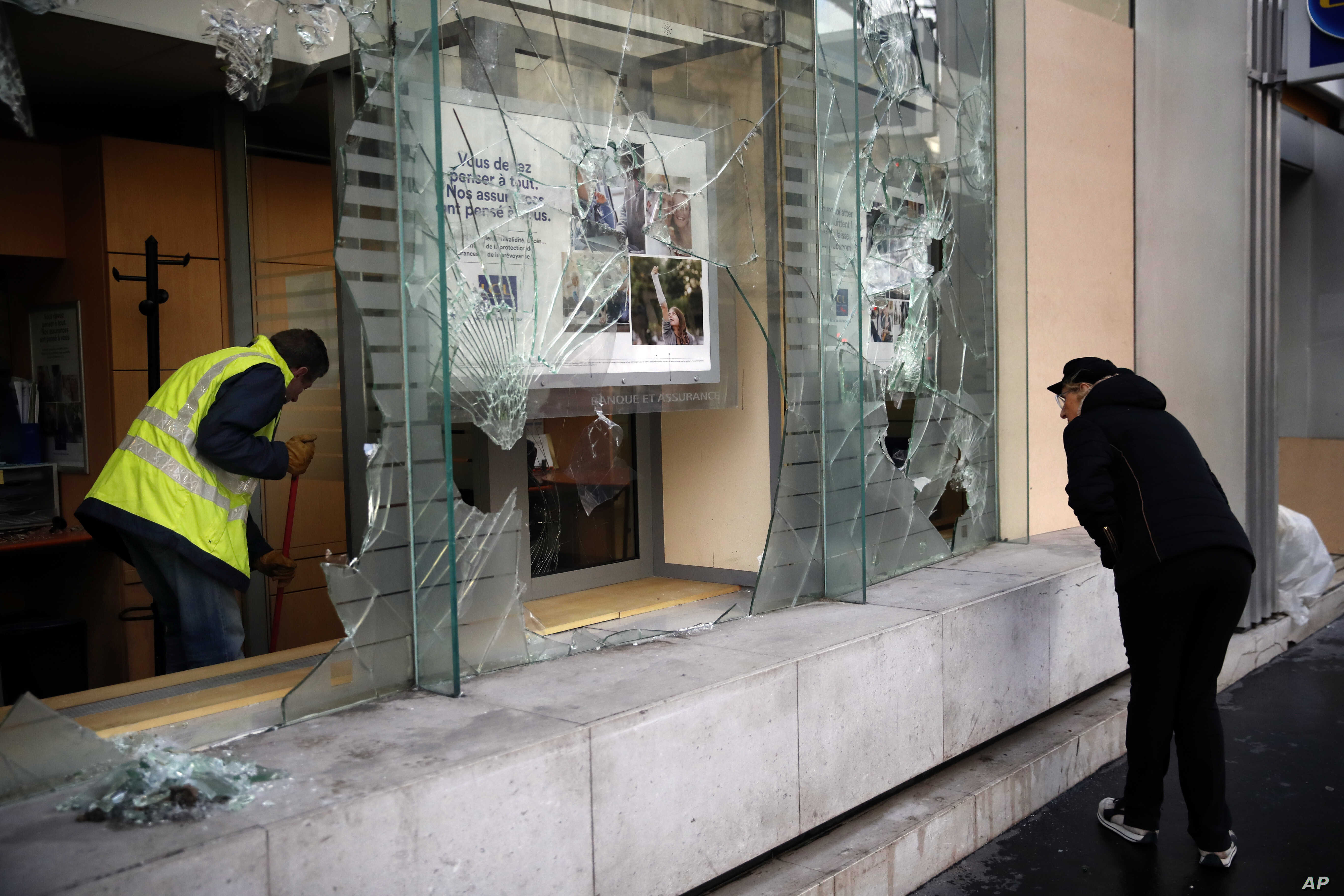 A worker clears debris in a bank as a man watches through smashed windows, in Paris, Sunday, Dec. 9, 2018.