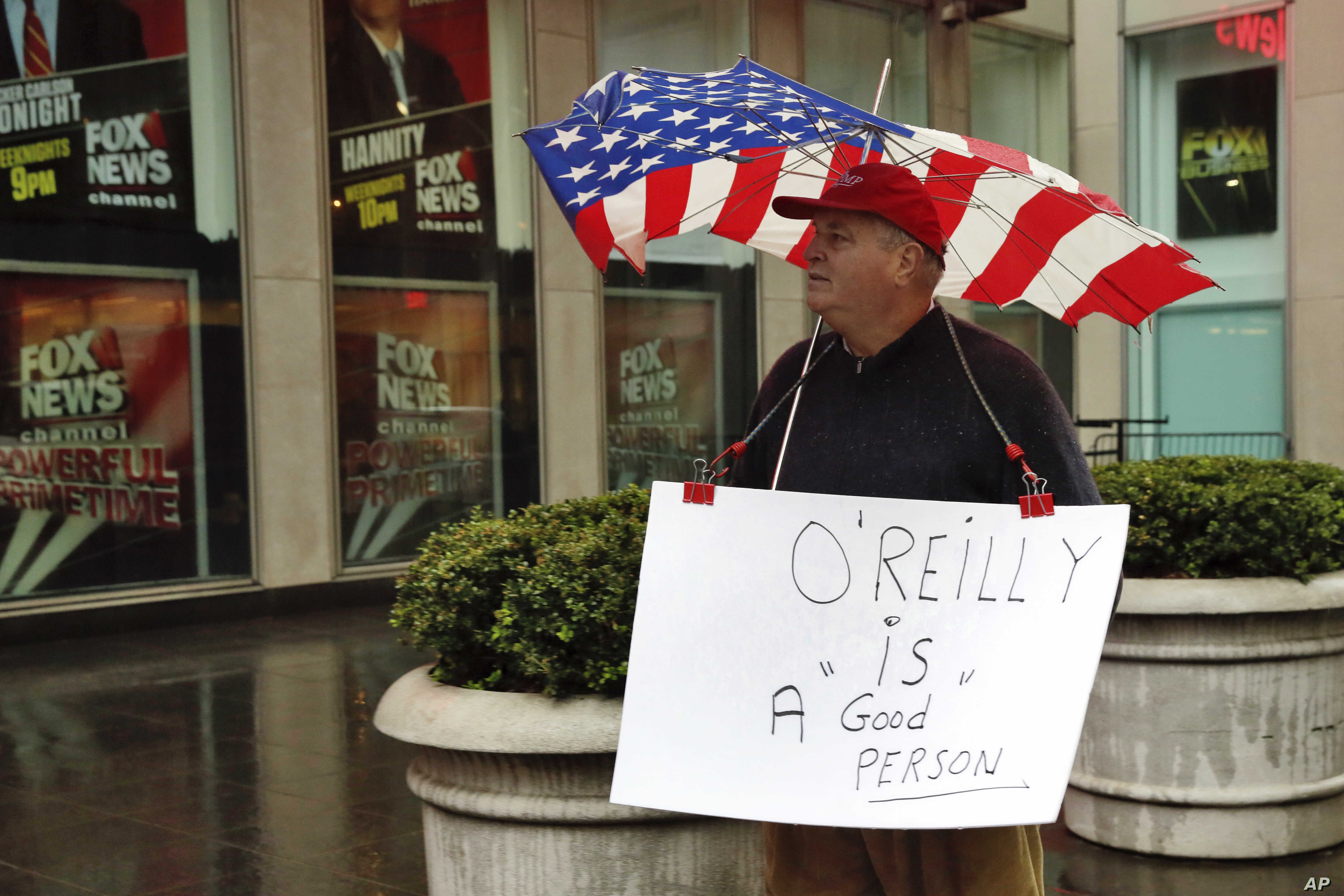 Douglas Esposit, of New York City, wears a Bill O'Reilly sign as he walks by the Fox television studios in New York, April 20, 2017. Despite the inglorious end to O'Reilly's two-decade Fox News Channel career, observers say his deep imprint on Fox an...