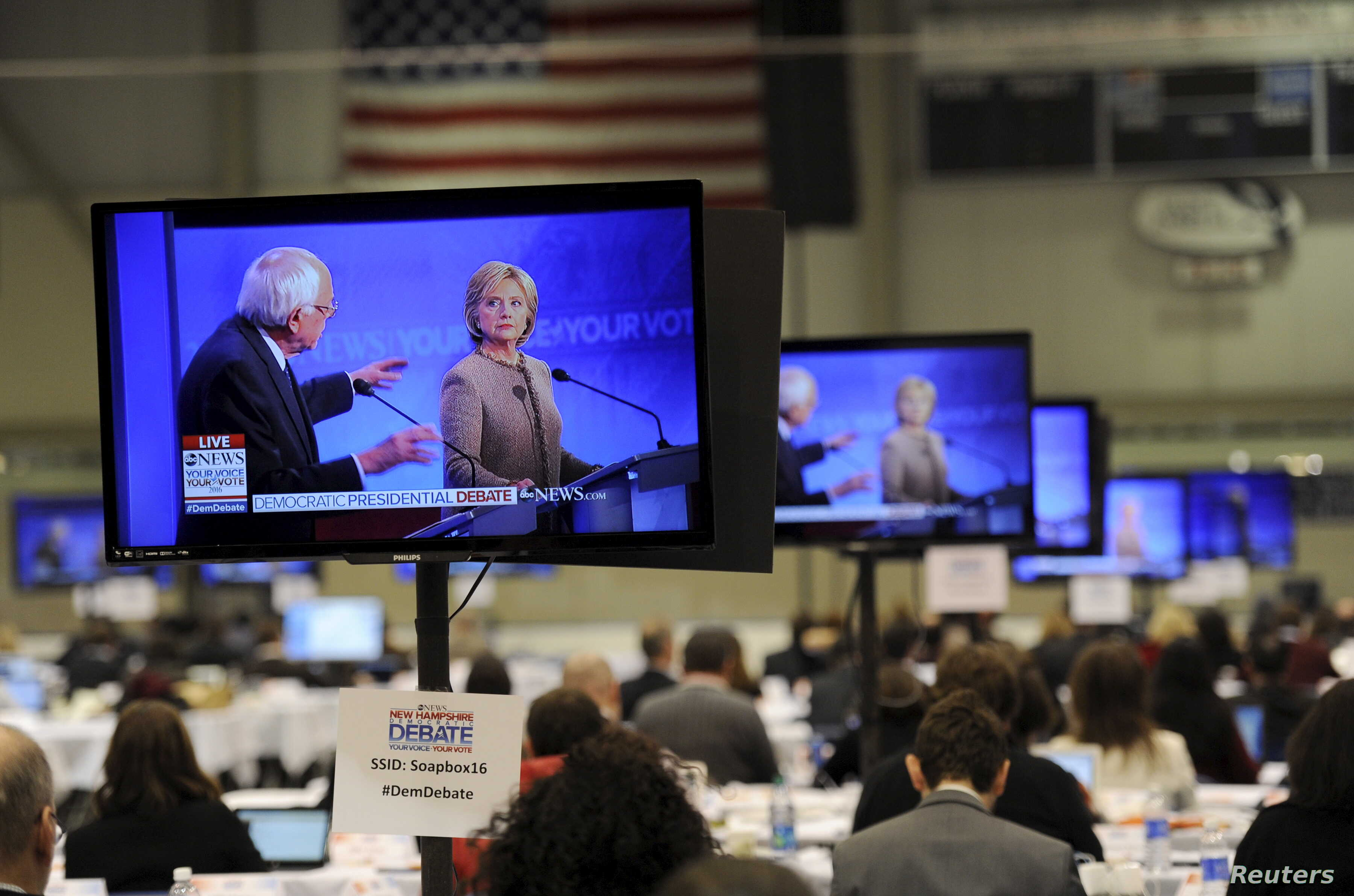 US Democratic presidential candidates Hillary Clinton and Bernie Sanders appear on television screens in the media work-room during the Democratic presidential candidates debate.