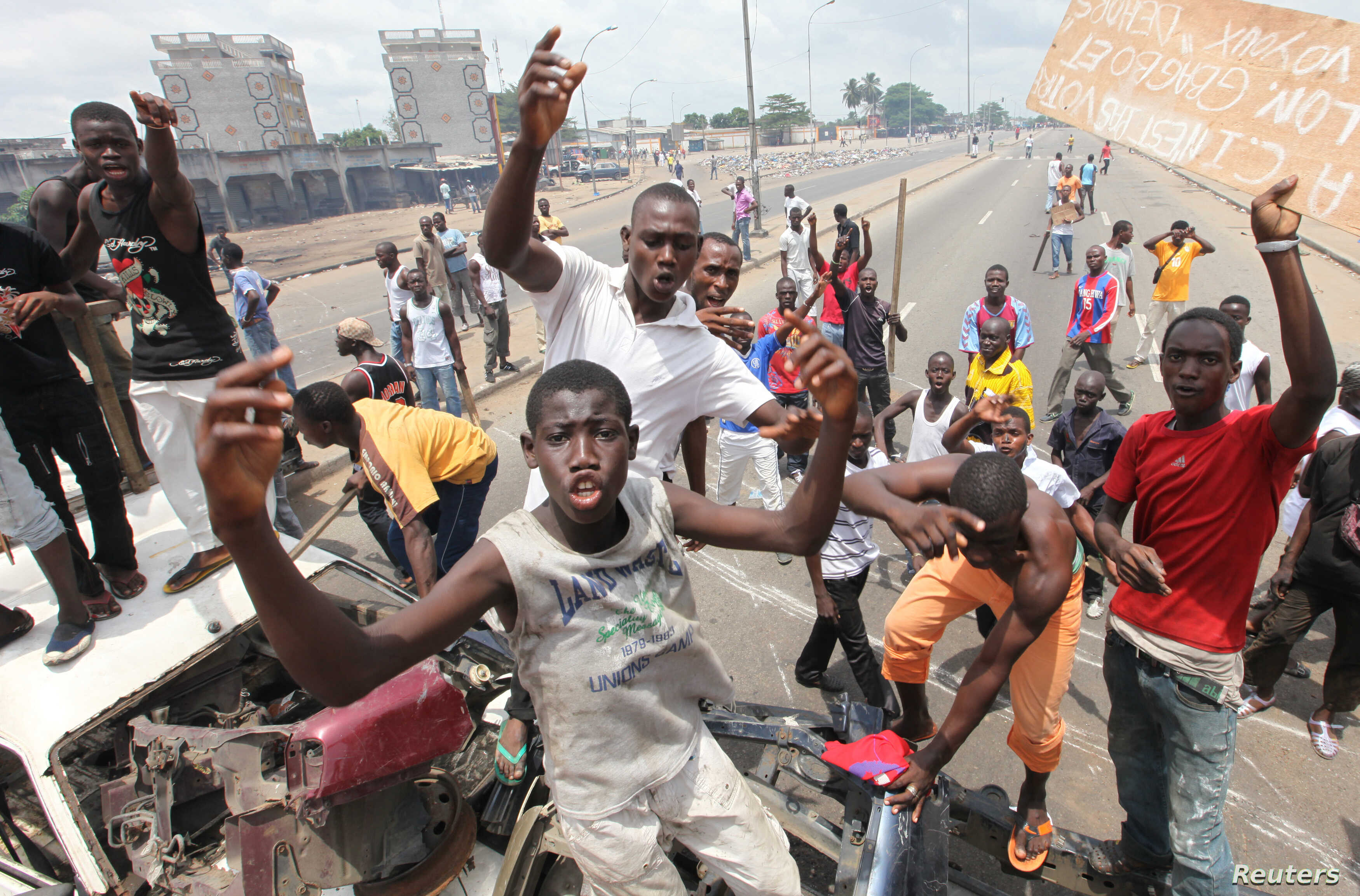 Anti-Gbagbo protesters stand near a roadblock and burning tires in the Abobo area of Abidjan, Ivory Coast, March 3, 2011.