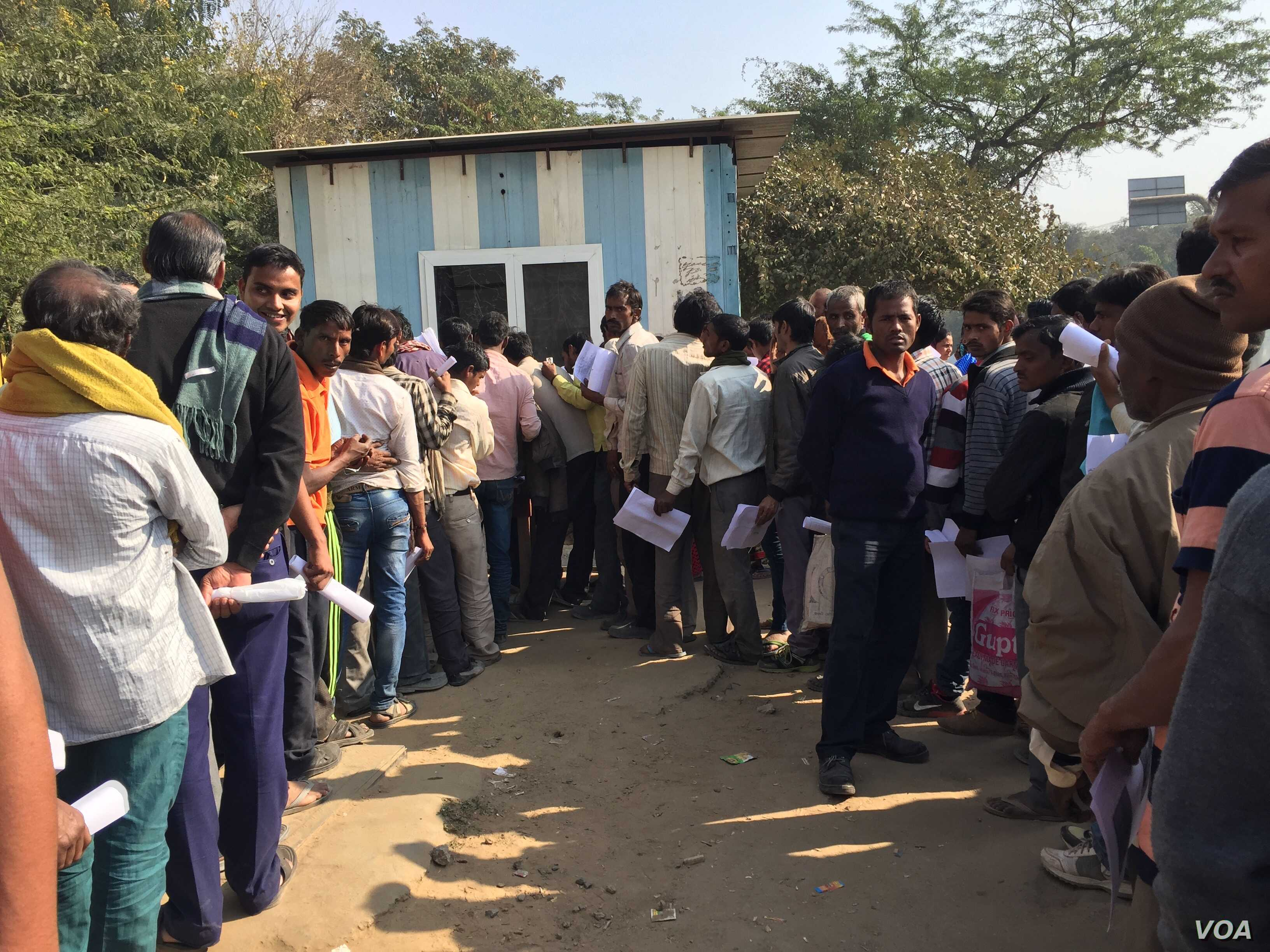 : Scores of workers in the informal sector line up along a busy intersection in the business hub of Gurgaon near New Delhi where a bank has opened a temporary camp to open new accounts as employers are unable to pay them in cash.