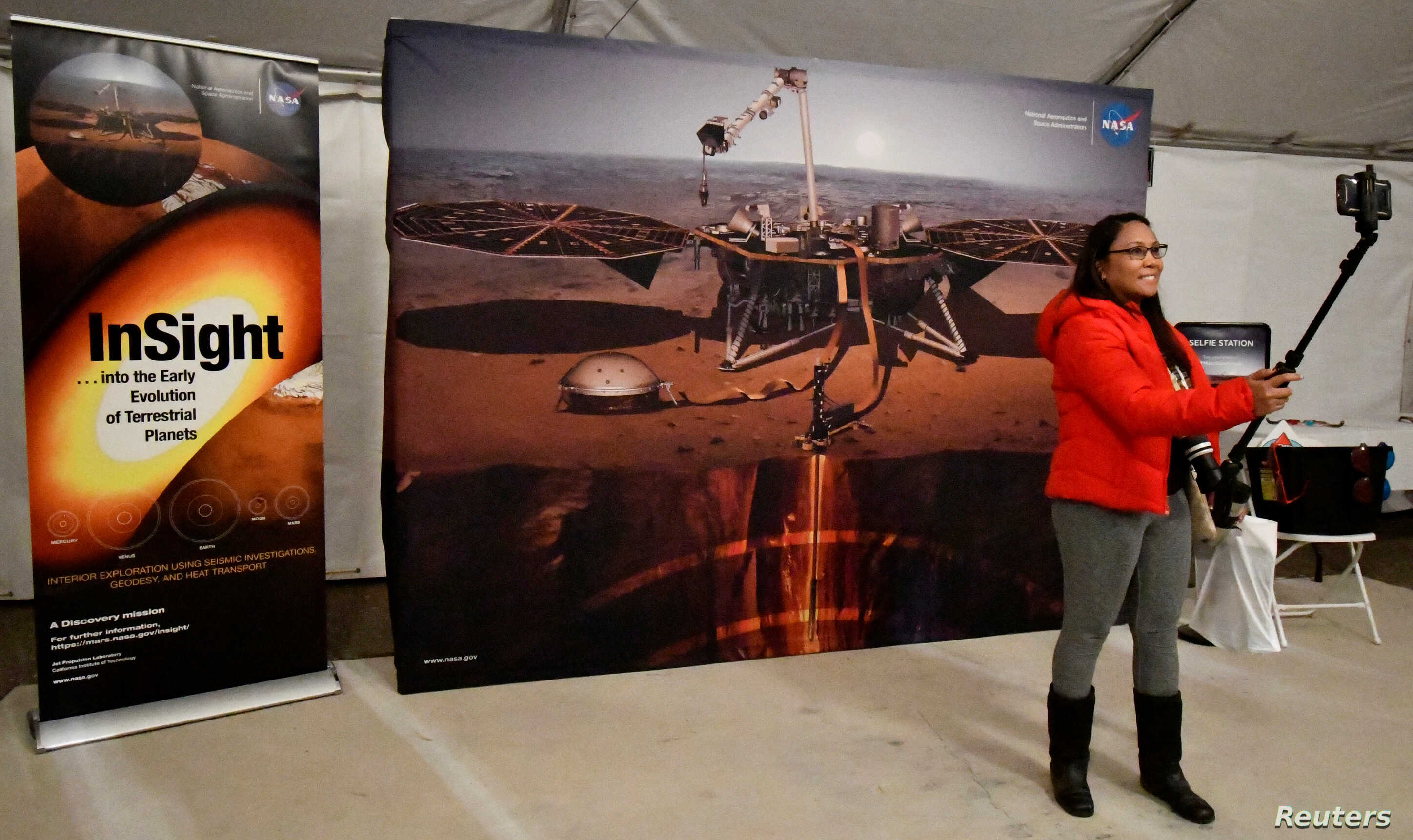 FILE - A visitor records herself at a NASA display at the Lompoc Airport before the launch of a United Launch Alliance Atlas V rocket carrying NASA's InSight Mars lander, which lifted off from Vandenberg Air Force Base in California, May 5, 2018.