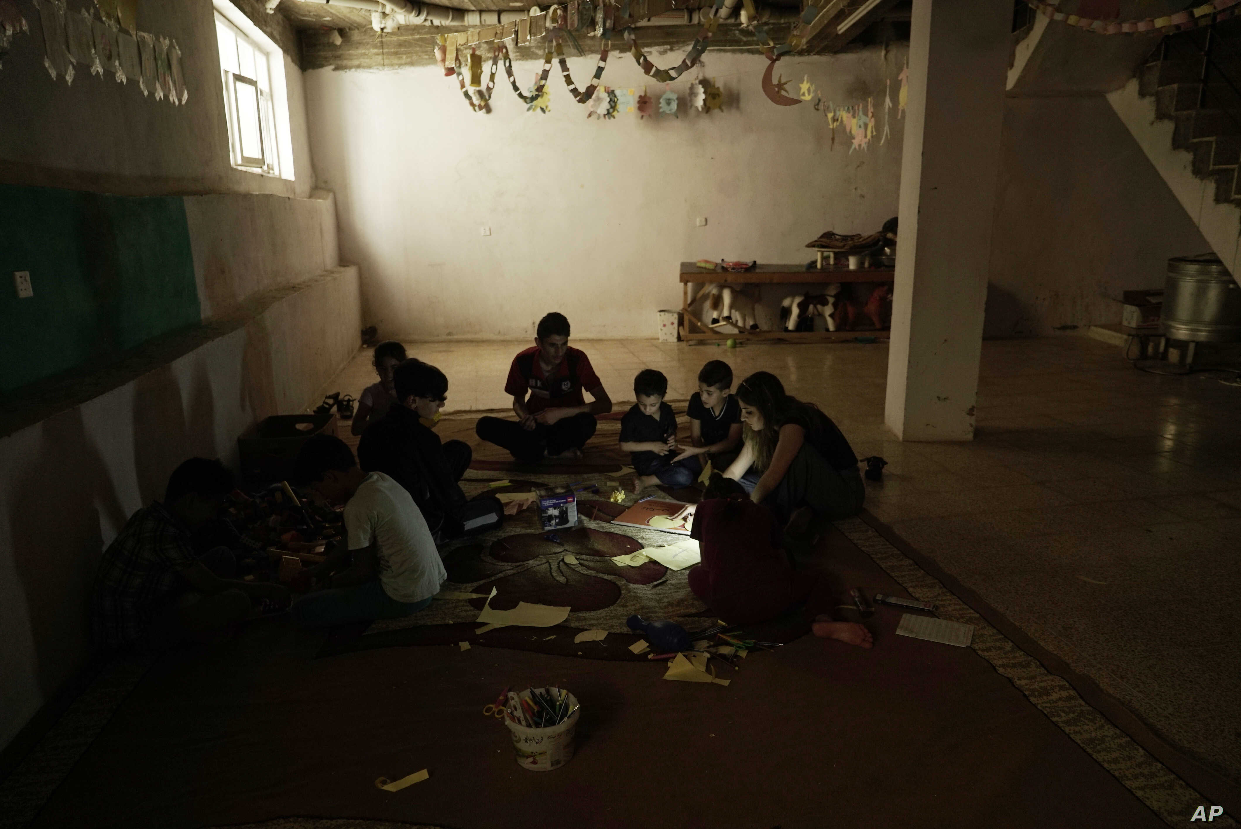 In this Aug. 22, 2018 photo, Yazidi children work on arts and crafts in the basement of an orphanage in Sheikhan, Iraq.