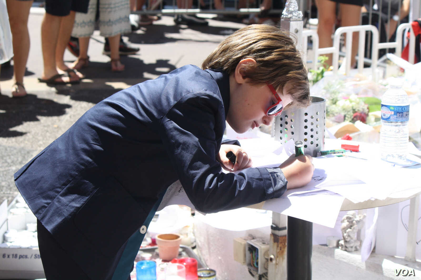 A boy writes a note of solidarity for the victims of Thursday's attack that killed 84 people and wounded over 200 in Nice, France, July 16, 2016. (H.Murdock/VOA)