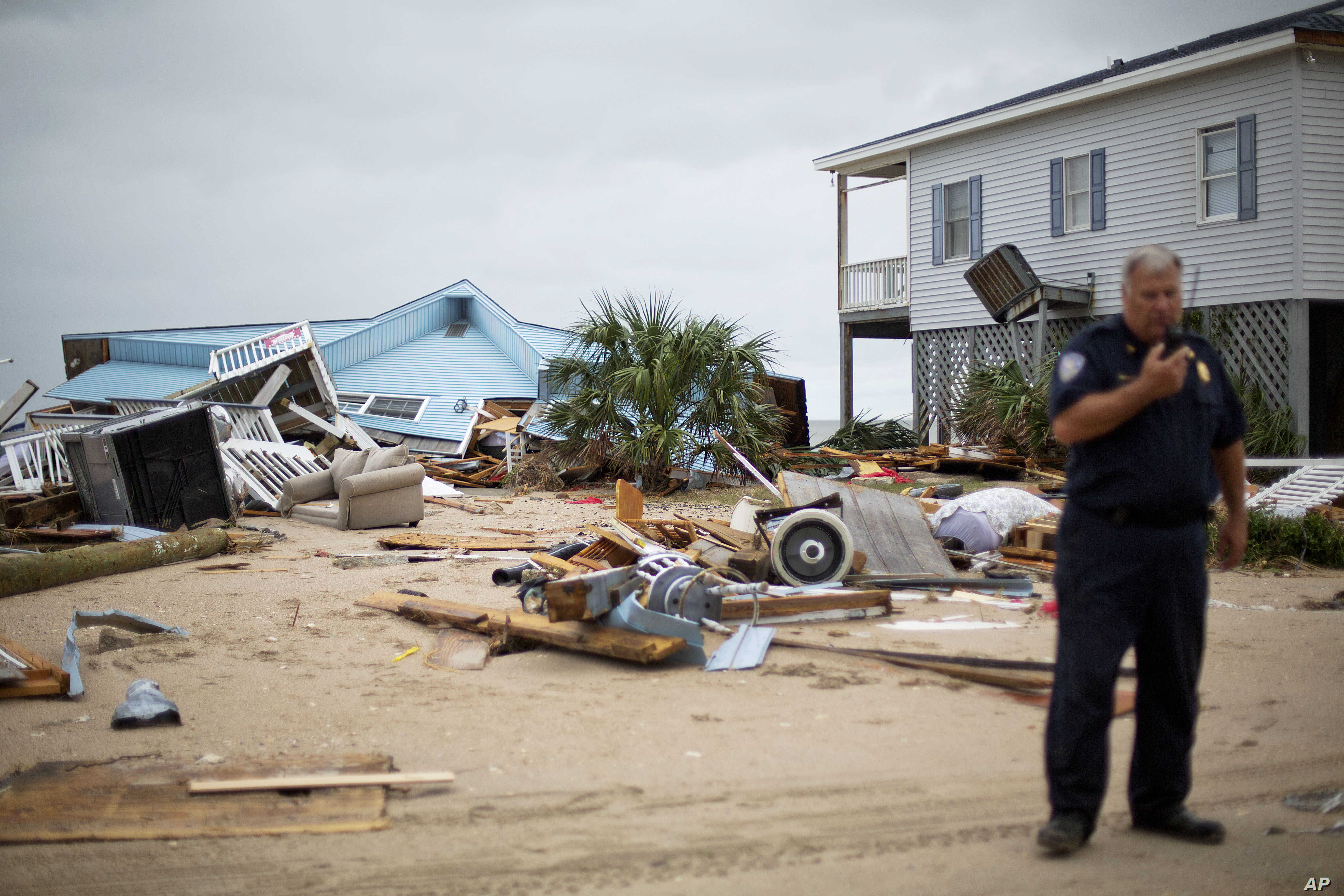 The remnants of a home leveled by Hurricane Matthew sit along the beachfront as Chief of Police George Brothers talks on the radio after Hurricane Matthew hit Edisto Beach, S.C., Oct. 8, 2016.