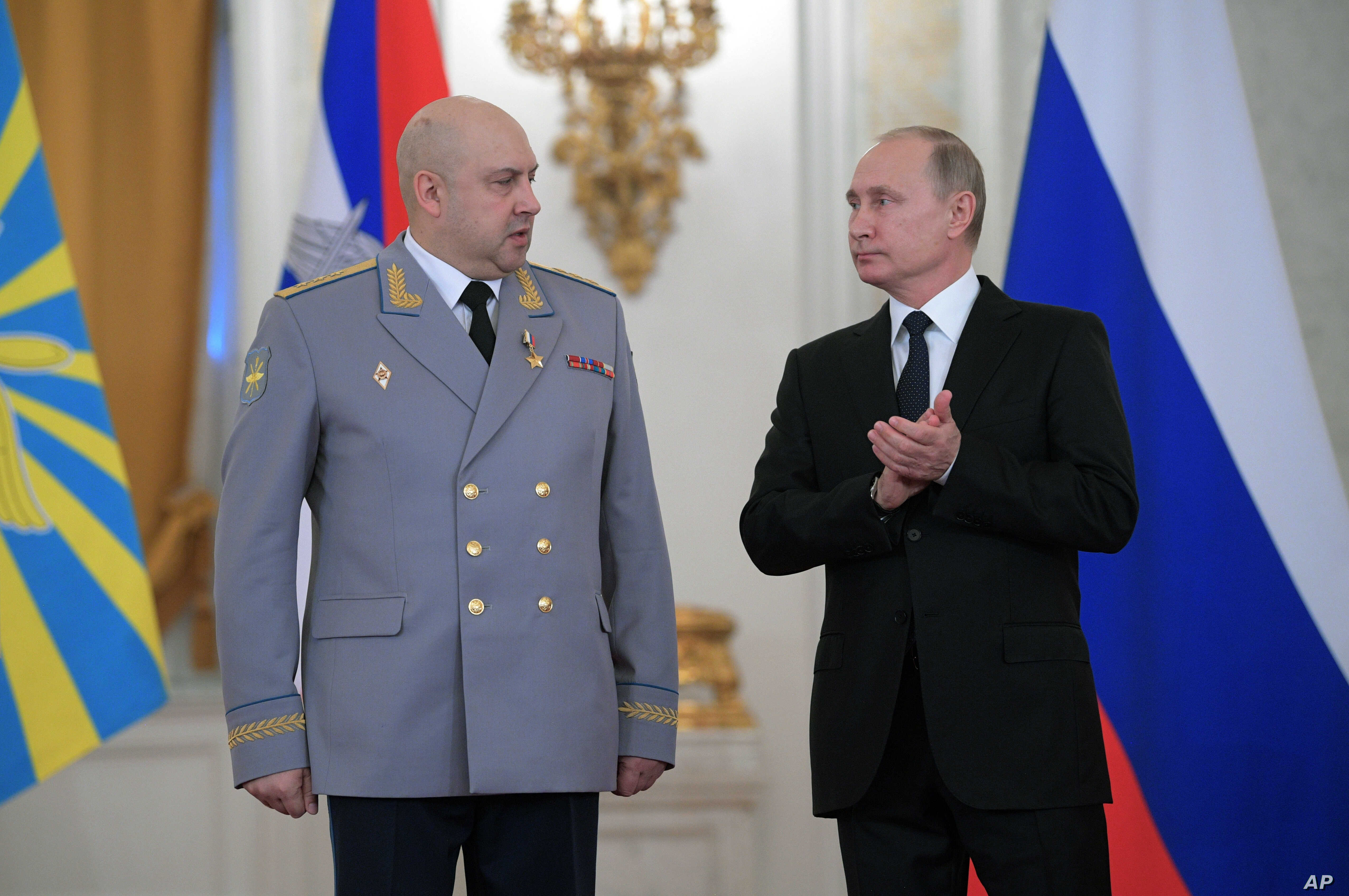 FILE - Russian President Vladimir Putin, right, applauds Col. Gen. Sergei Surovikin during an awards ceremony for troops who fought in Syria, in the Kremlin, in Moscow, Dec. 28, 2017. Putin says Russia's action in Syria has demonstrated the power of ...