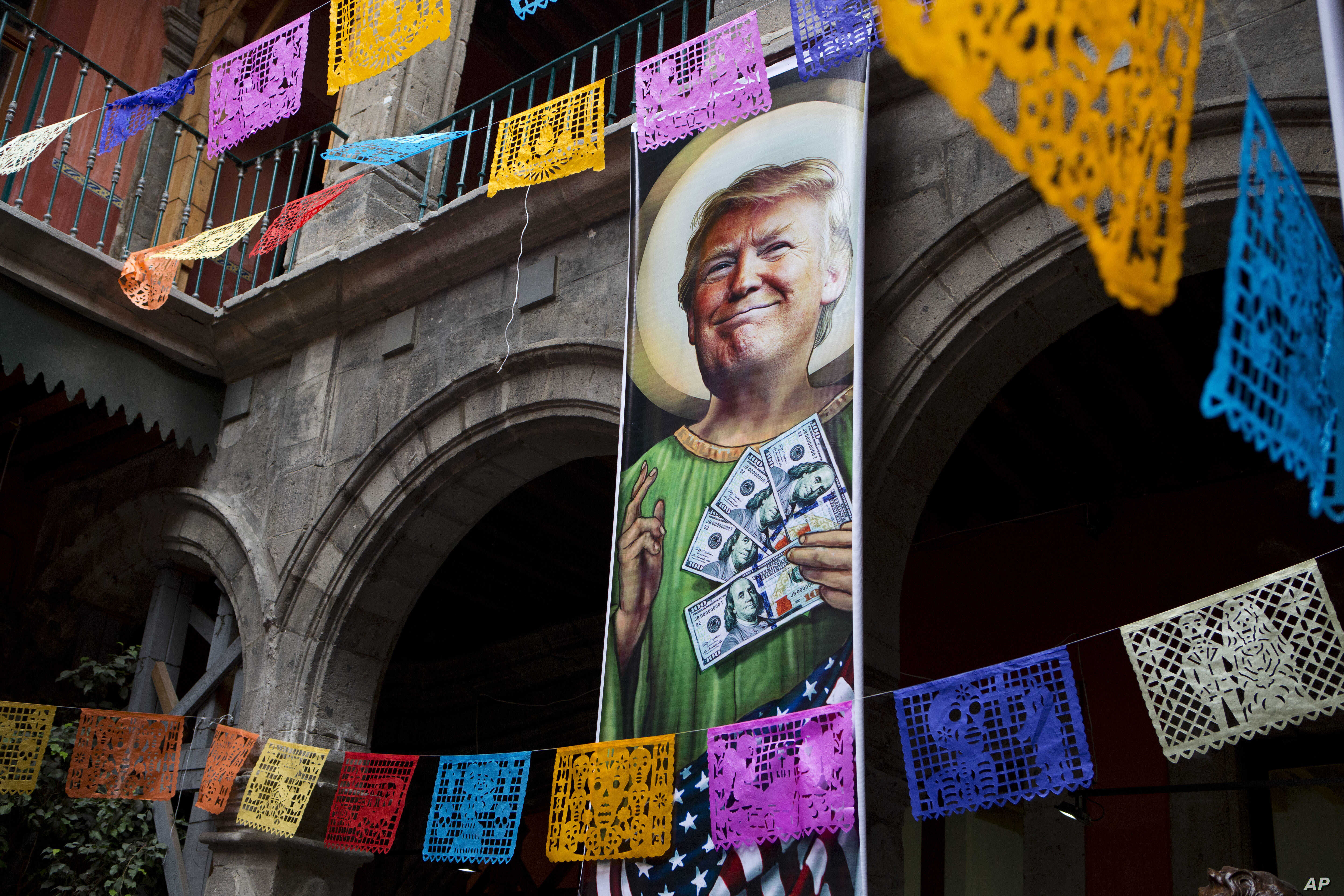 FILE - A banner with an image of Donald Trump promotes an exhibition that features dozens of works by Mexican and international cartoonists, mocking among other things the U.S. president's derogatory statements about Mexicans and his plans to build a...