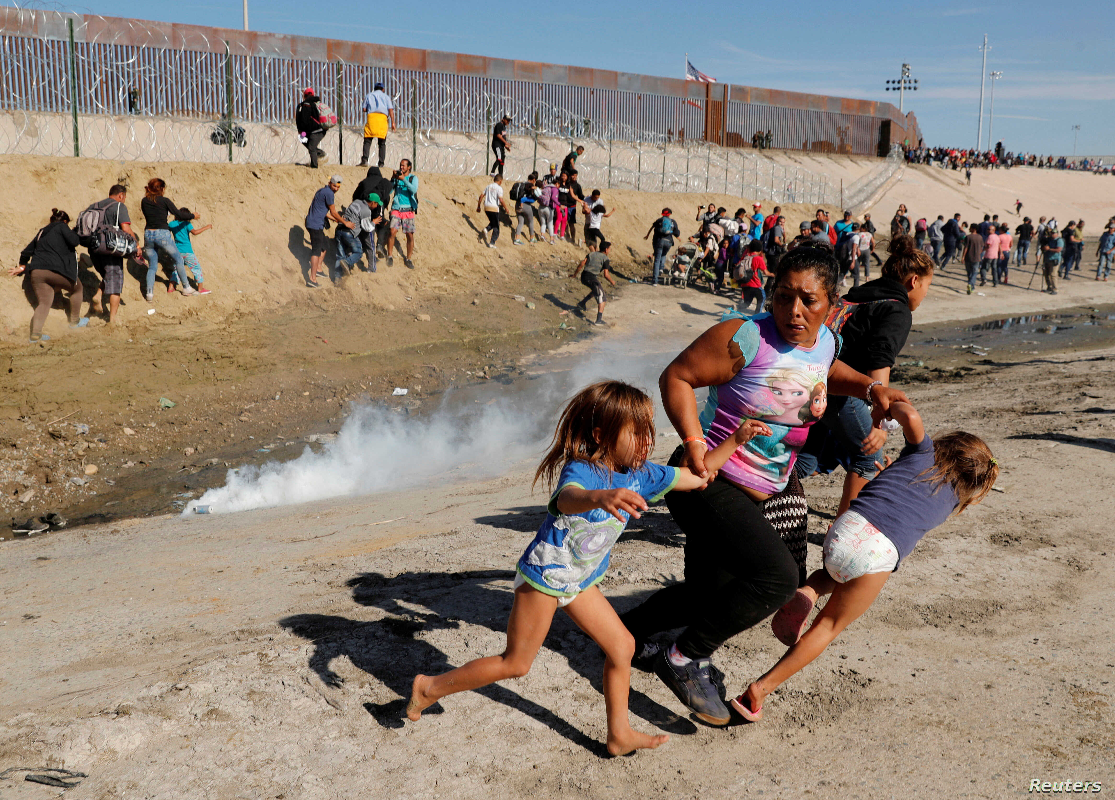 Maria Lila Meza Castro (C), a 39-year-old migrant woman from Honduras, runs away from tear gas with her five-year-old twin daughters Saira Nalleli Mejia Meza (L) and Cheili Nalleli Mejia Meza (R) in front of the border wall between the U.S and Mexico