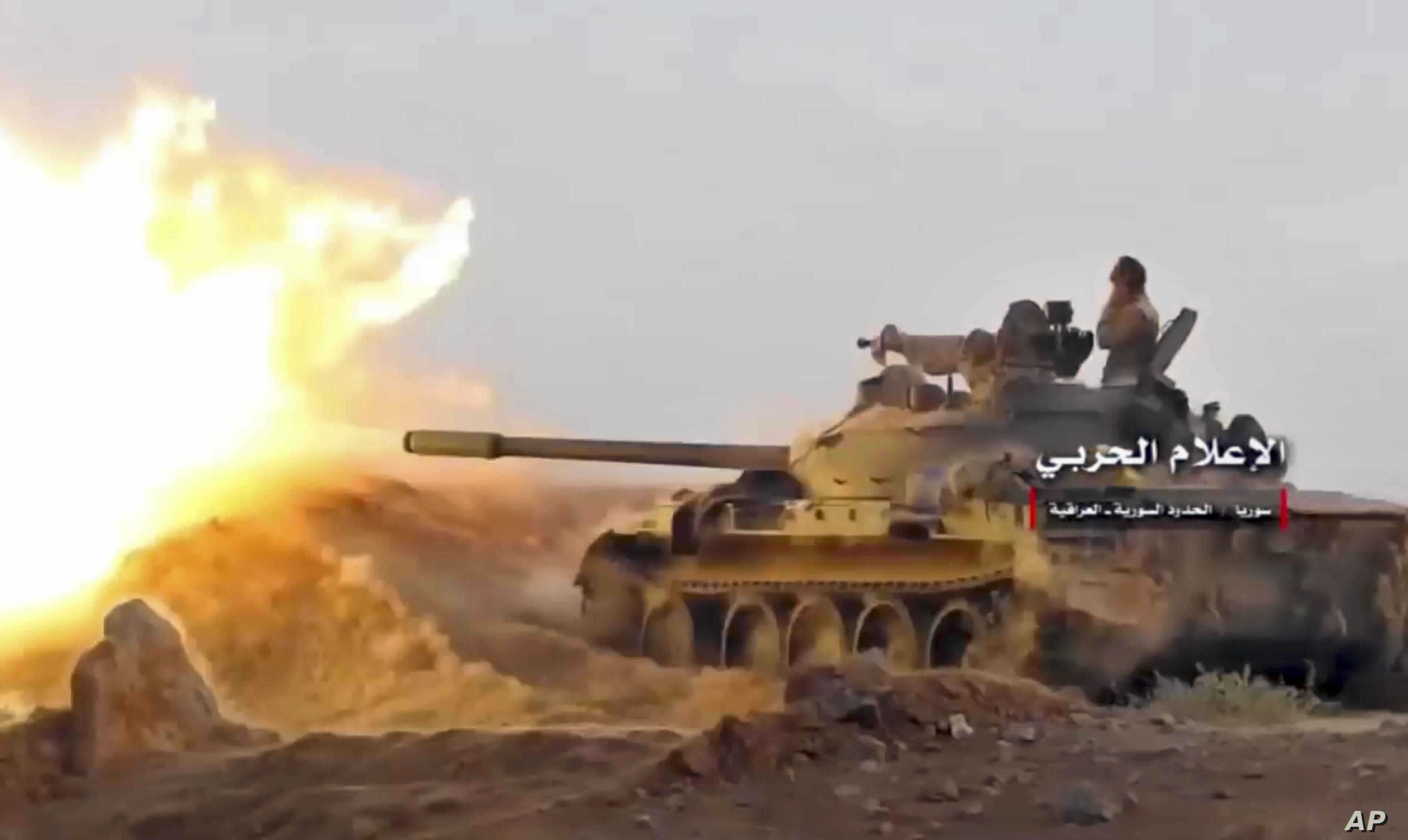 This frame grab from video provided Nov 8, 2017, by the government-controlled Syrian Central Military Media, shows a tank firing on militants' positions on the Iraq-Syria border.