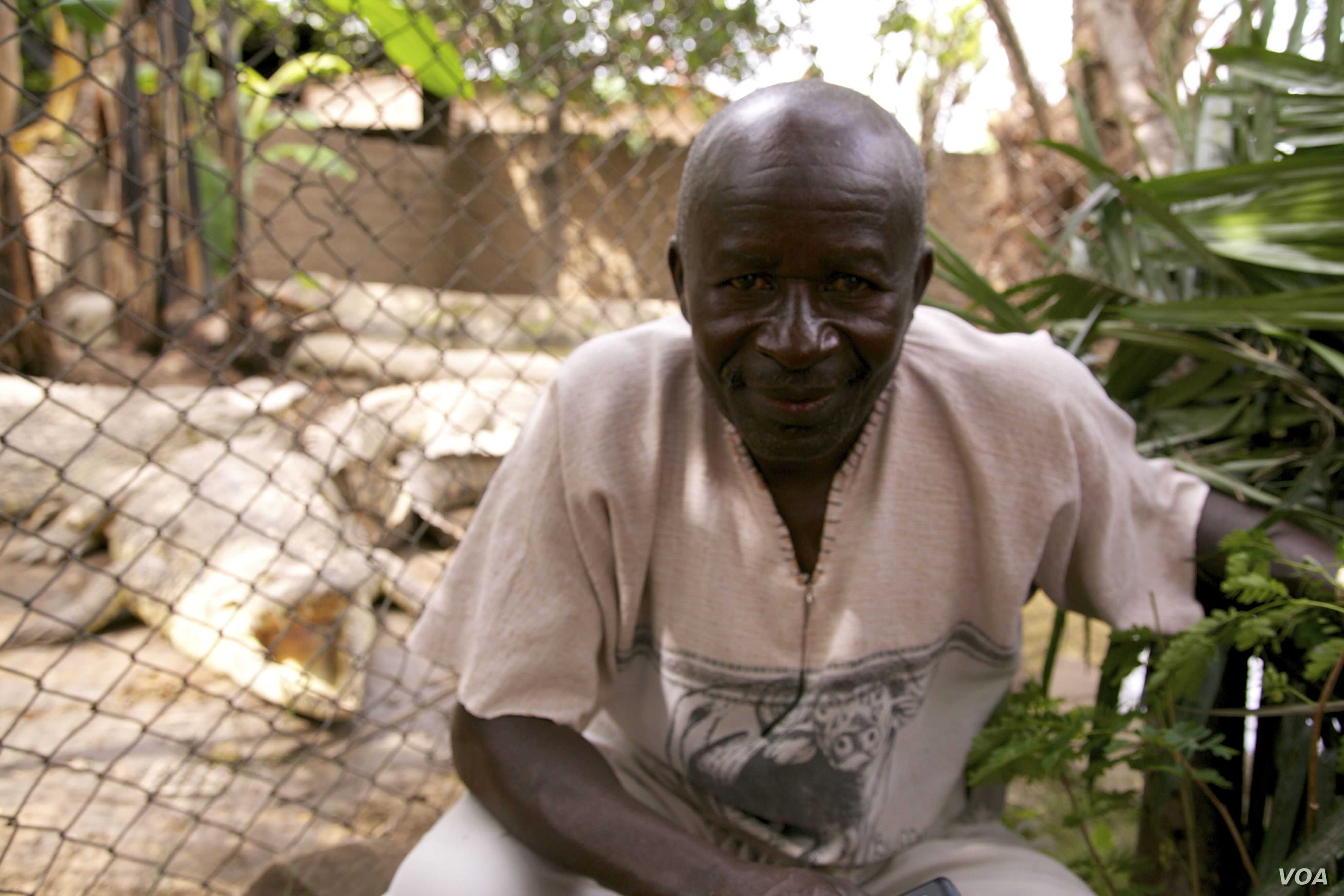 Burundian Albert  Ngendera poses with his pets, eight crocodiles that will soon become over 40 and no longer fit on his porch. (VOA / H. McNeish)