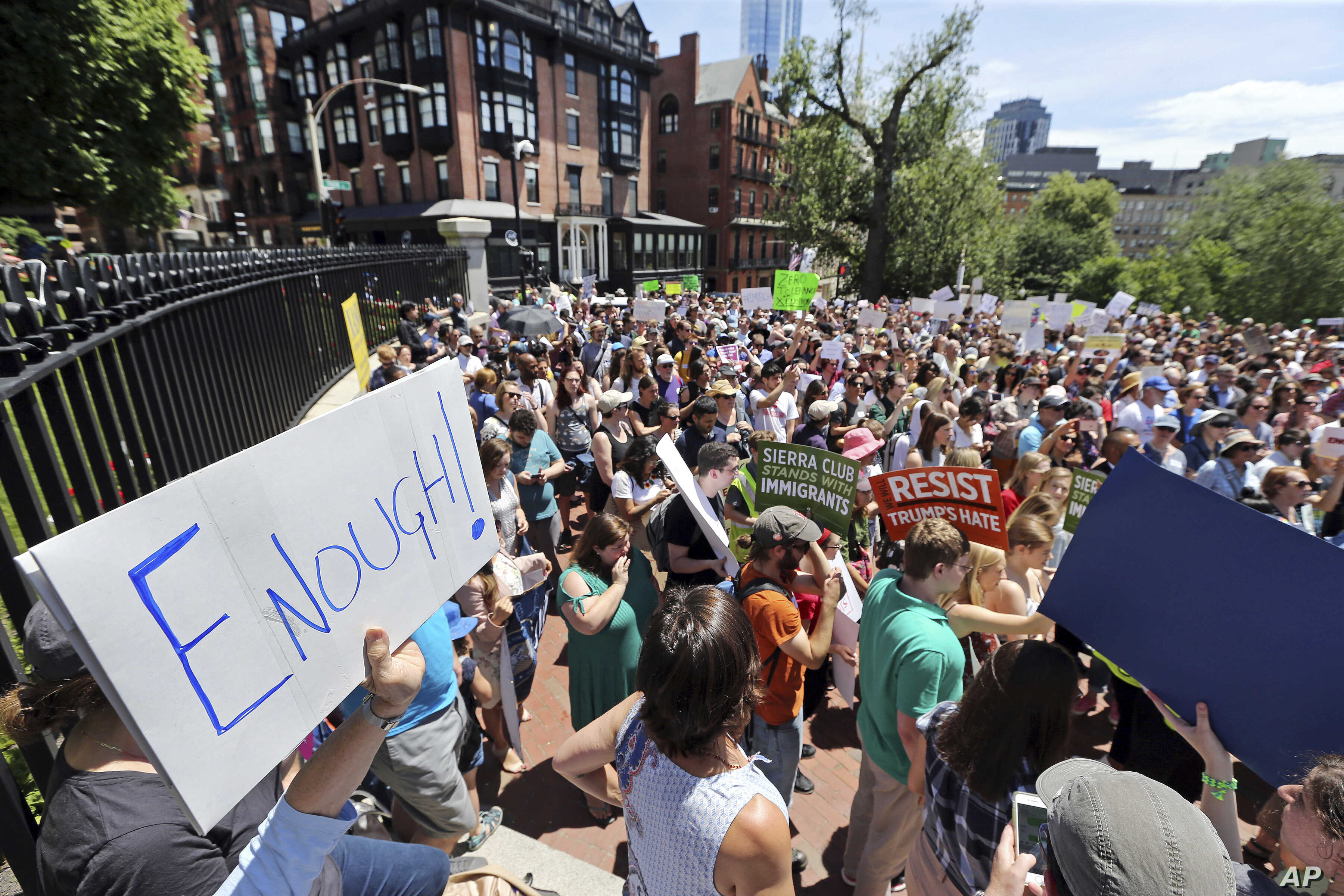 People rally outside the Statehouse, in Boston, June 20, 2018, to protest how immigrants are being treated both on the border with Mexico and in Massachusetts.