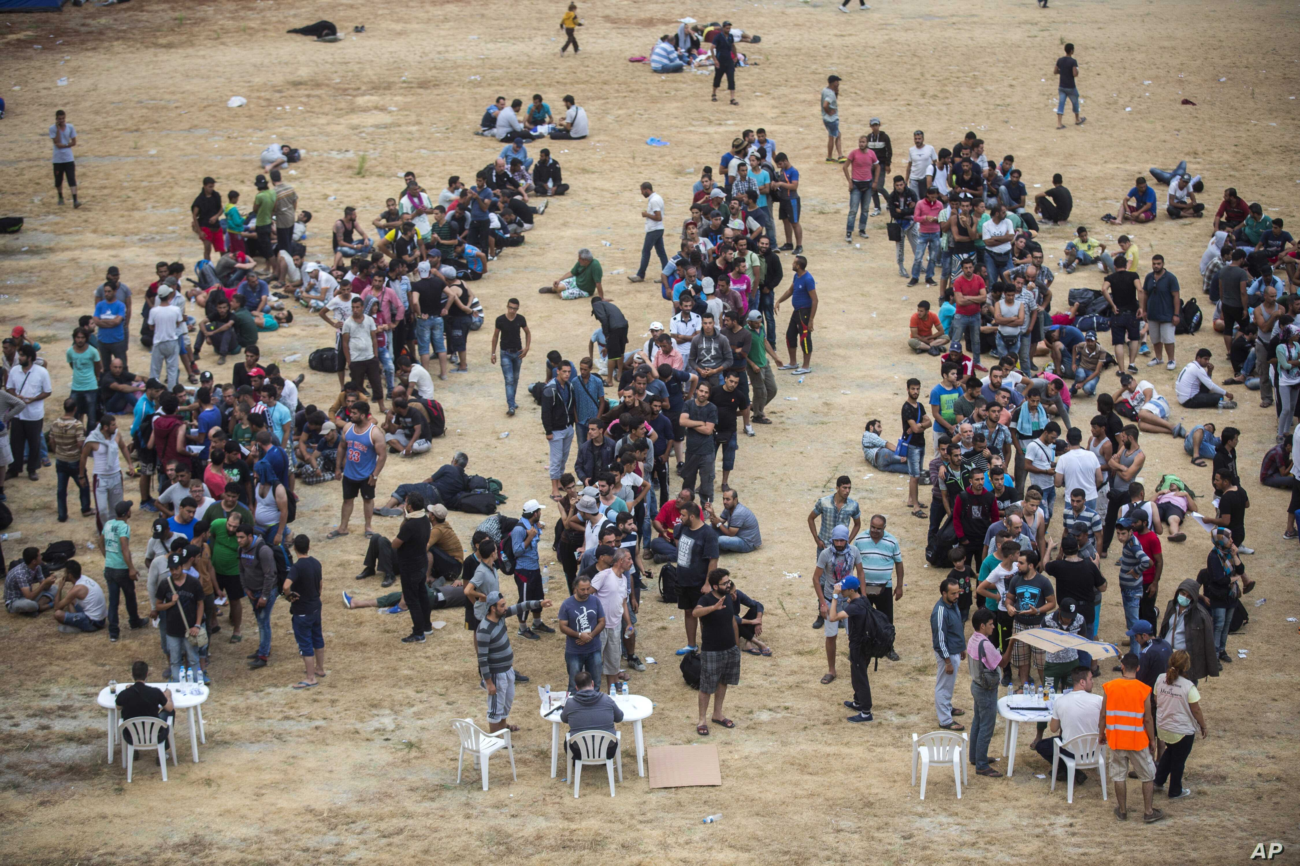 Refugees and migrants wait for their registration and the issuing of travel documents at a soccer stadium in Mytilene, on the northeastern Greek island of Lesbos, Sept. 8, 2015.