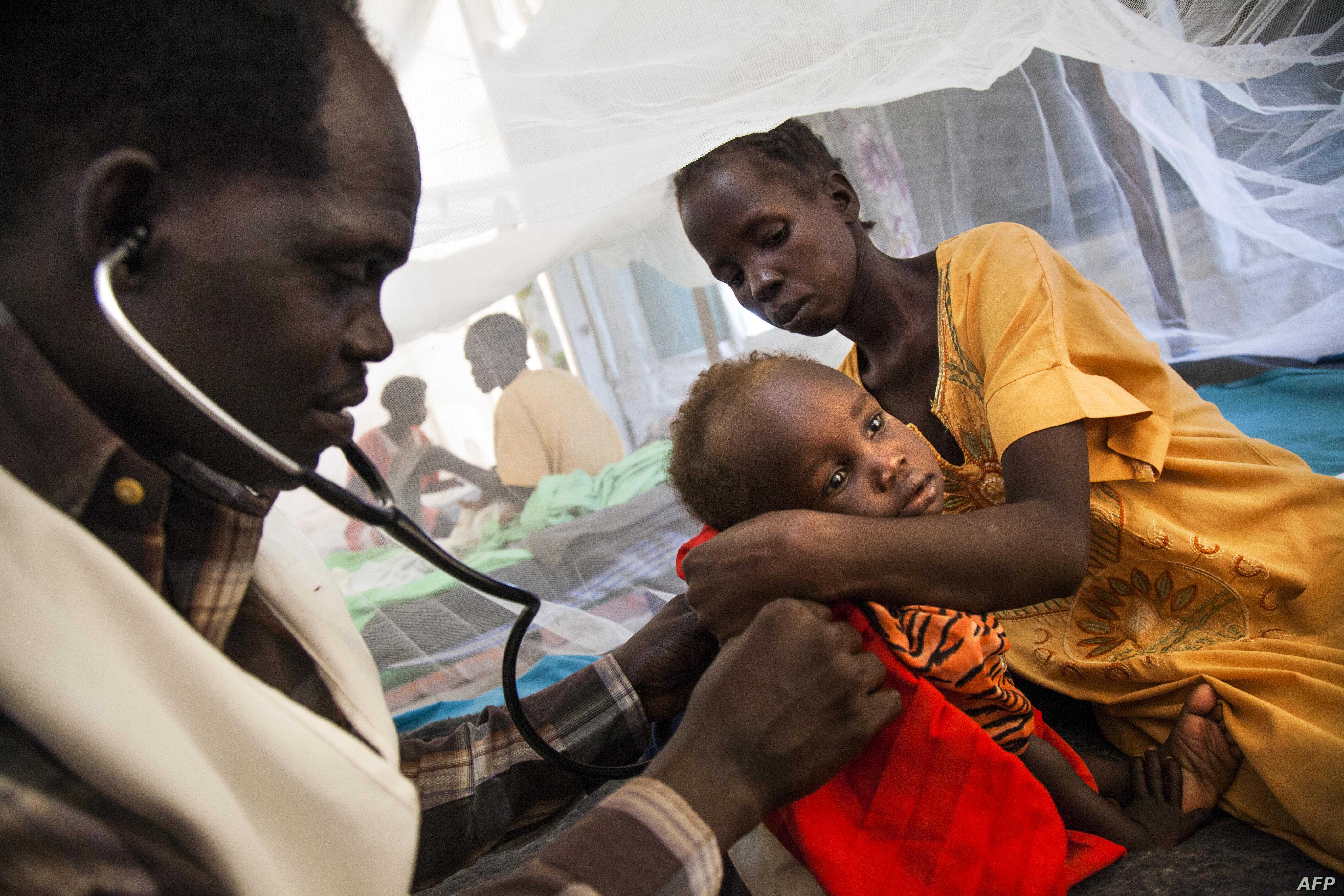 Doctor Simon Angelo (L) examines Iman Steven suffering from tuberculosis, held by her mother (R) at the hospital of Doctors Without Borders (MSF) on June 15, 2016, at the Protection of Civilians (PoC) site in Malakal, South Sudan.