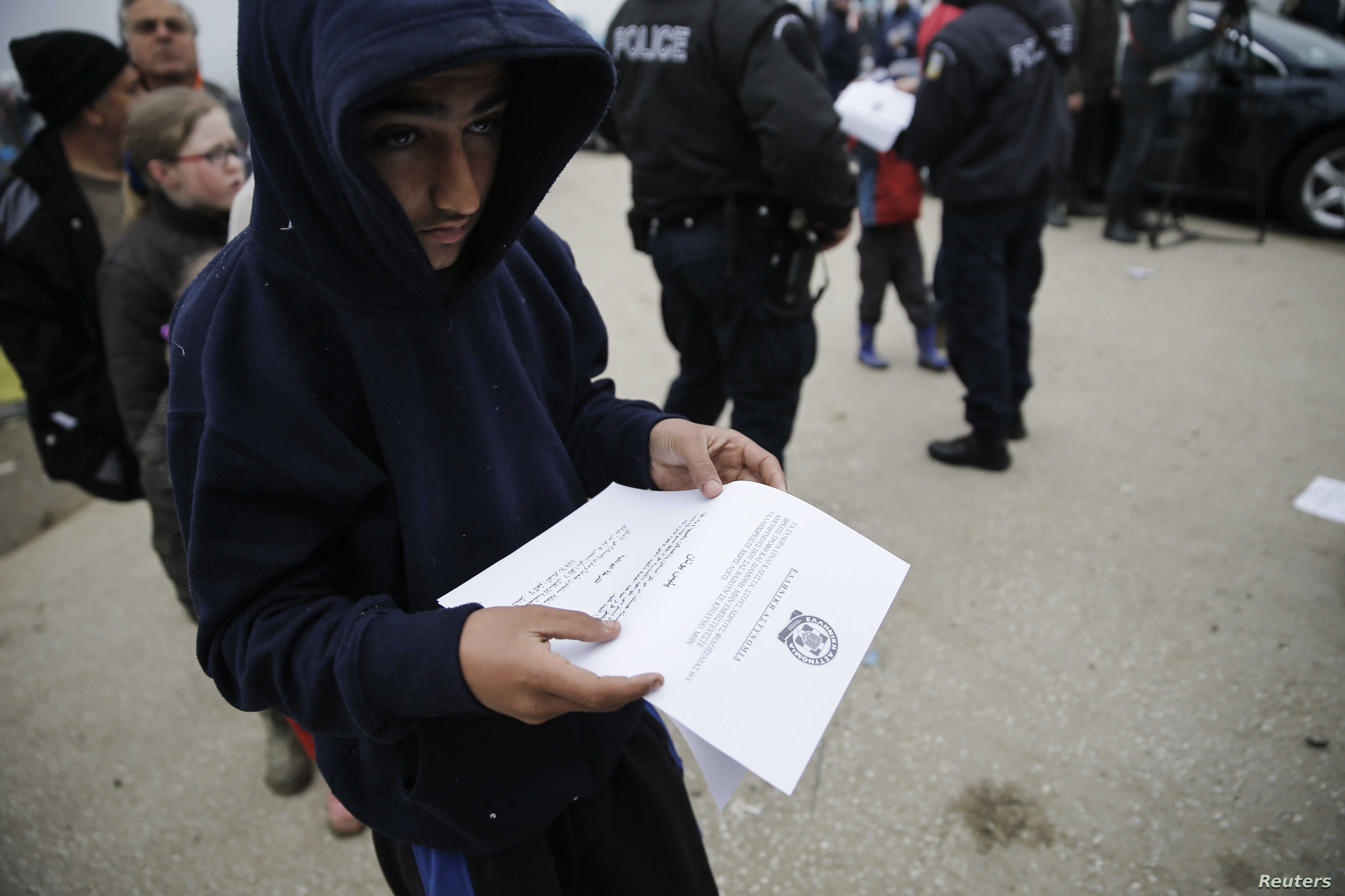 A boy reads an announcement distributed by Greek police officers informing refugees and migrants that the borders to Macedonia are closed and they should consider moving to relocation centers, at a makeshift camp at the Greek-Macedonian border near t...