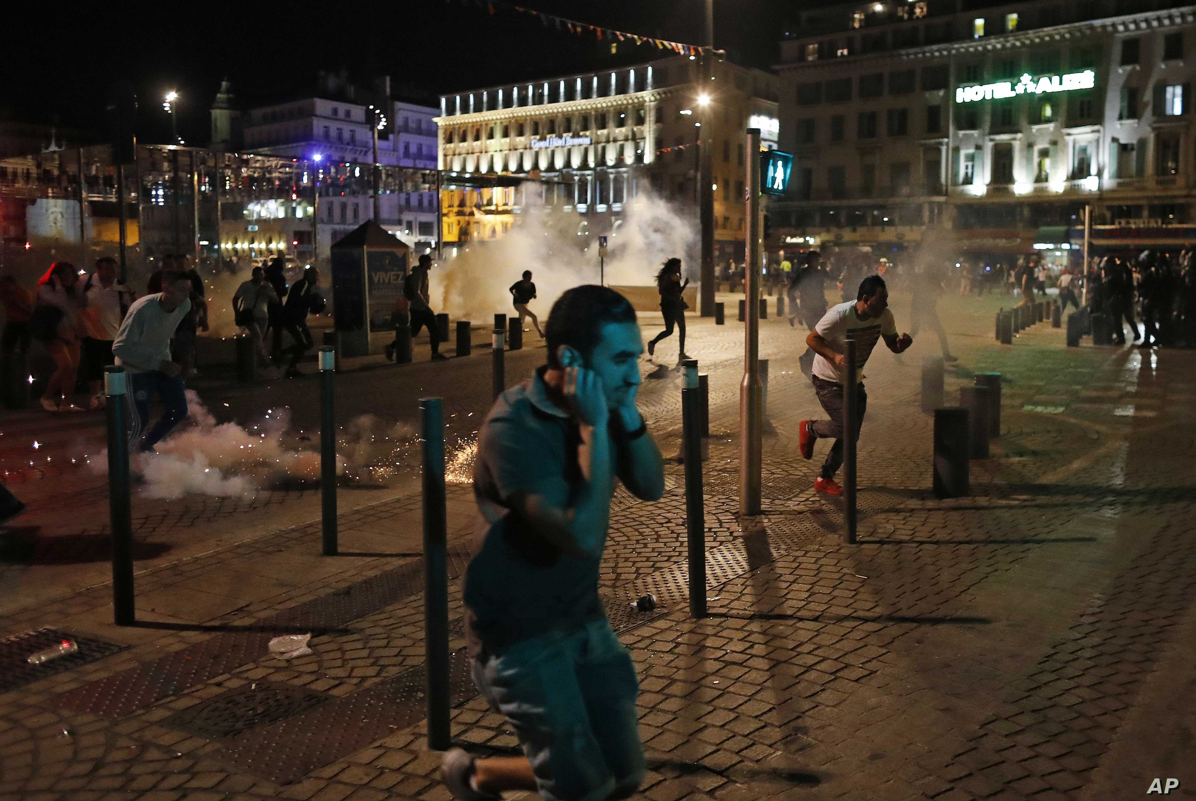 People run after police fired tear gas following clashes after the Euro 2016 soccer championship group B match between England and Russia in Marseille, France on June 11, 2016.