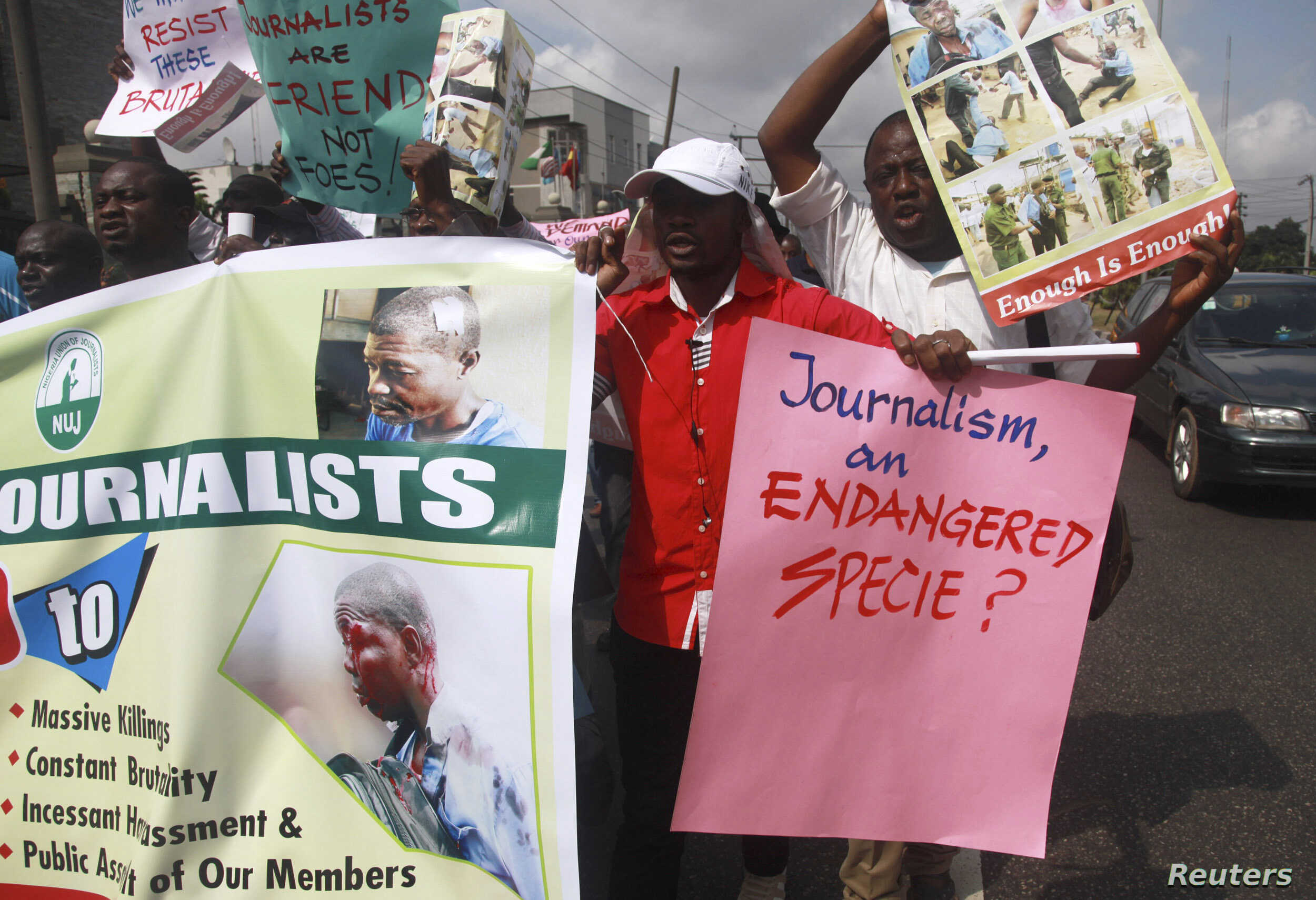 FILE - Journalists hold placards as they protest along a road days after a journalist was assaulted by mortuary attendants at the Lagos State University Teaching Hospital, in Lagos, Aug. 16, 2012.