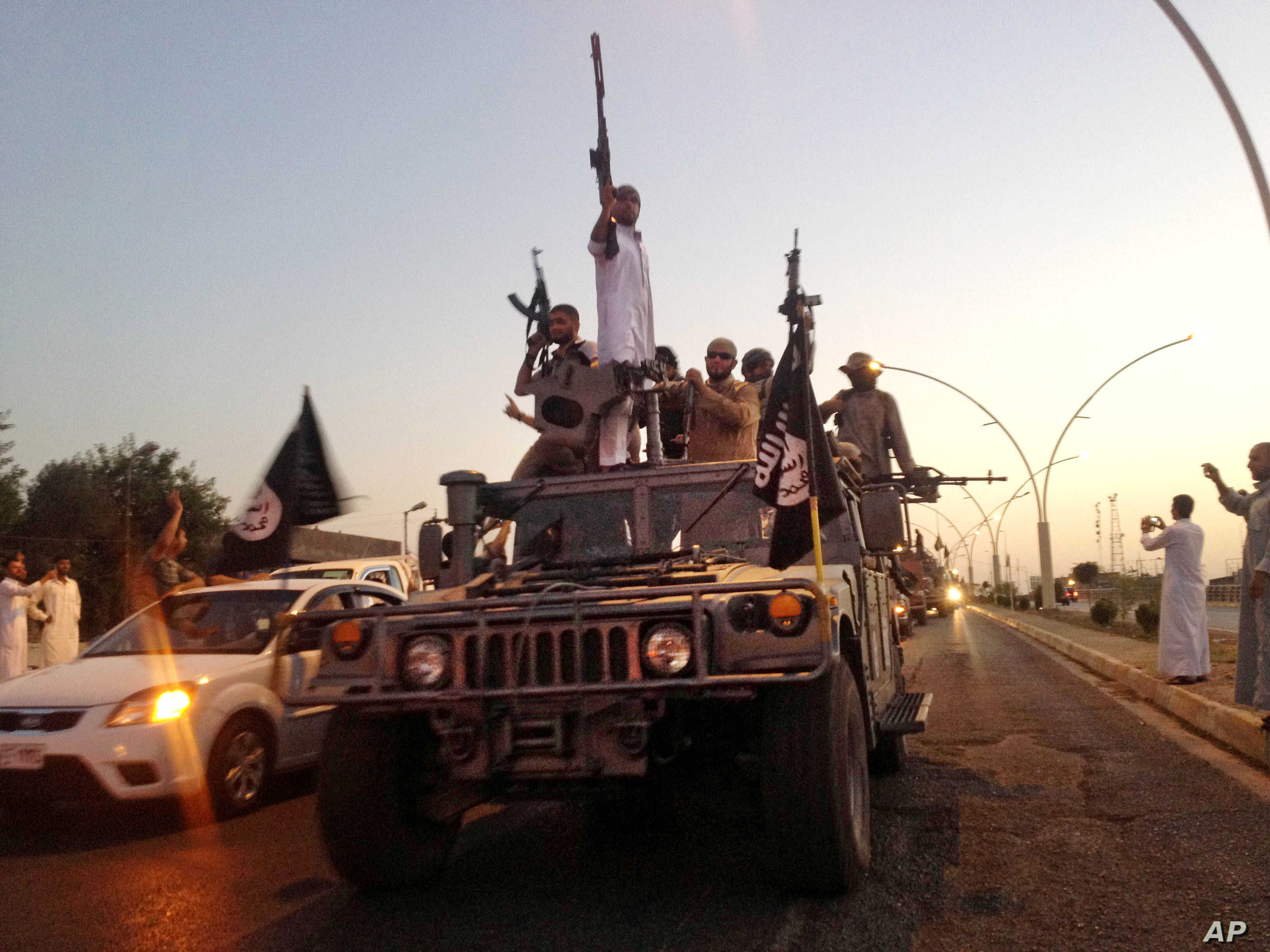 FILE - Fighters from the Islamic State group parade in a commandeered Iraqi security forces armored vehicle on the main road at the northern city of Mosul, Iraq, June 23, 2014.
