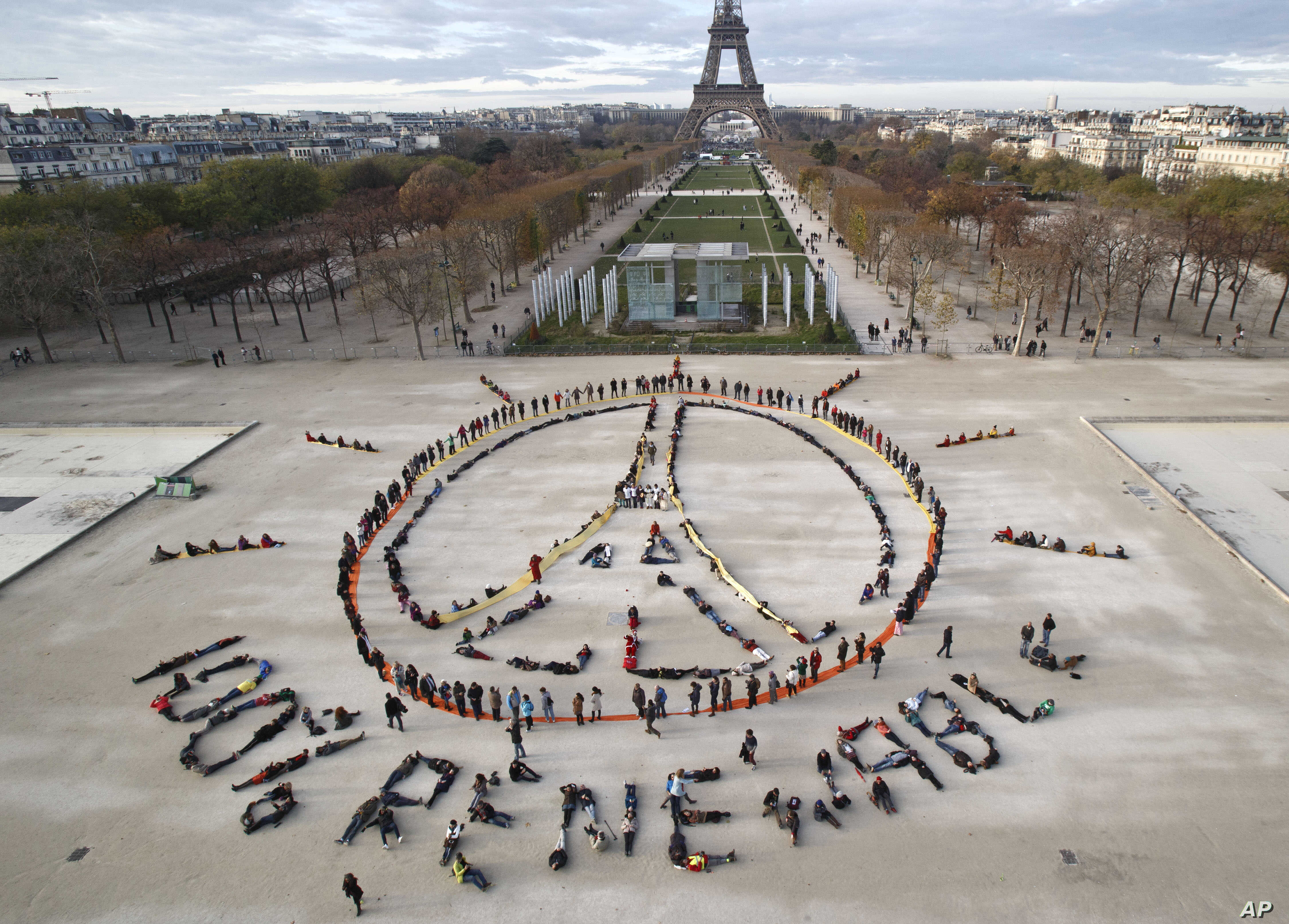 "FILE - In this Dec. 6, 2015 file photo, environmentalist activists form a human chain representing the peace sign and the spelling out ""100% renewable"", on the side line of the COP21, United Nations Climate Change Conference near the Eiffel Tower in"