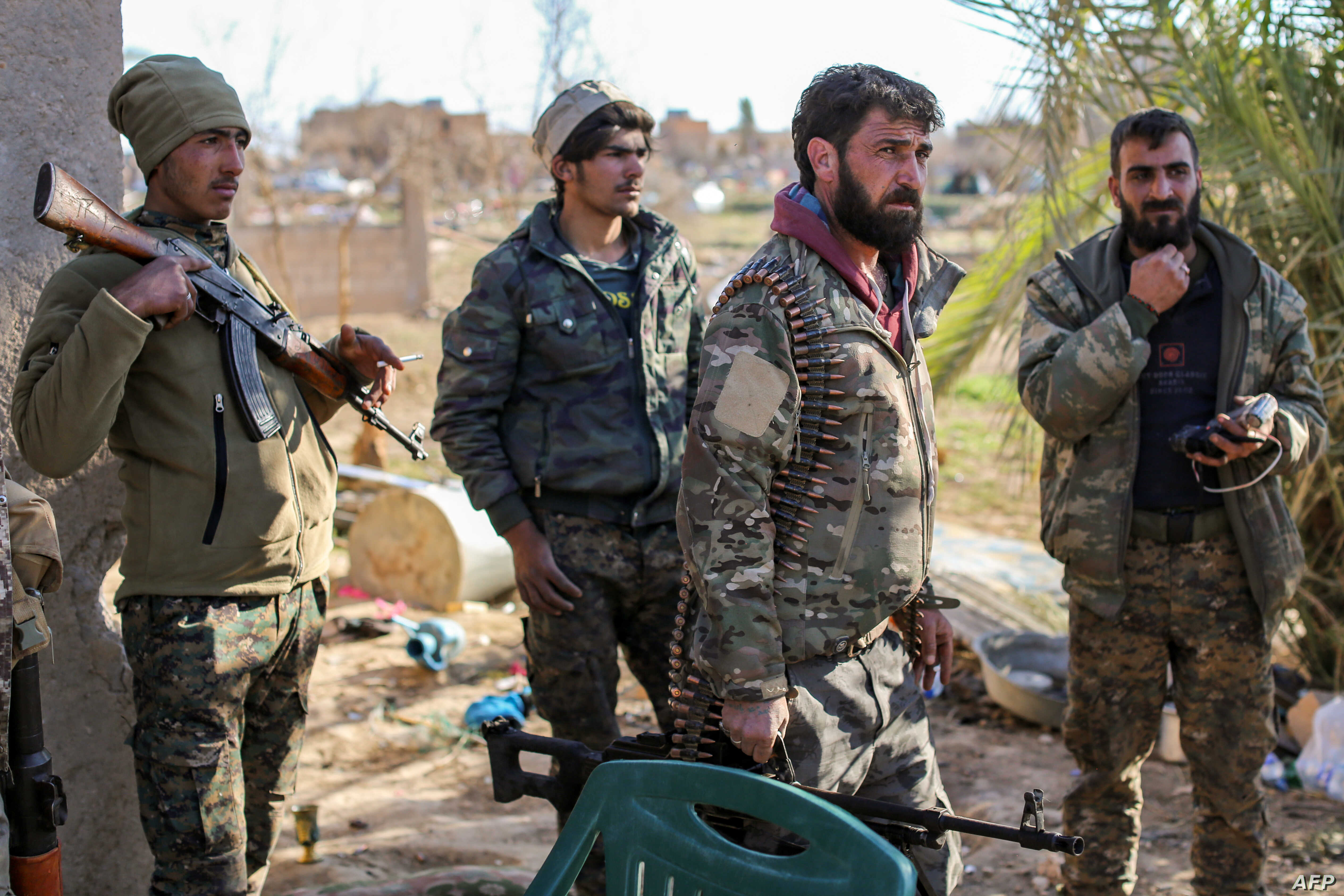 Fighters with the U.S.-backed Syrian Democratic Forces (SDF) check a makeshift camp for Islamic State (IS) group members and their families in the town of Baghuz, eastern Syria, March 9, 2019.