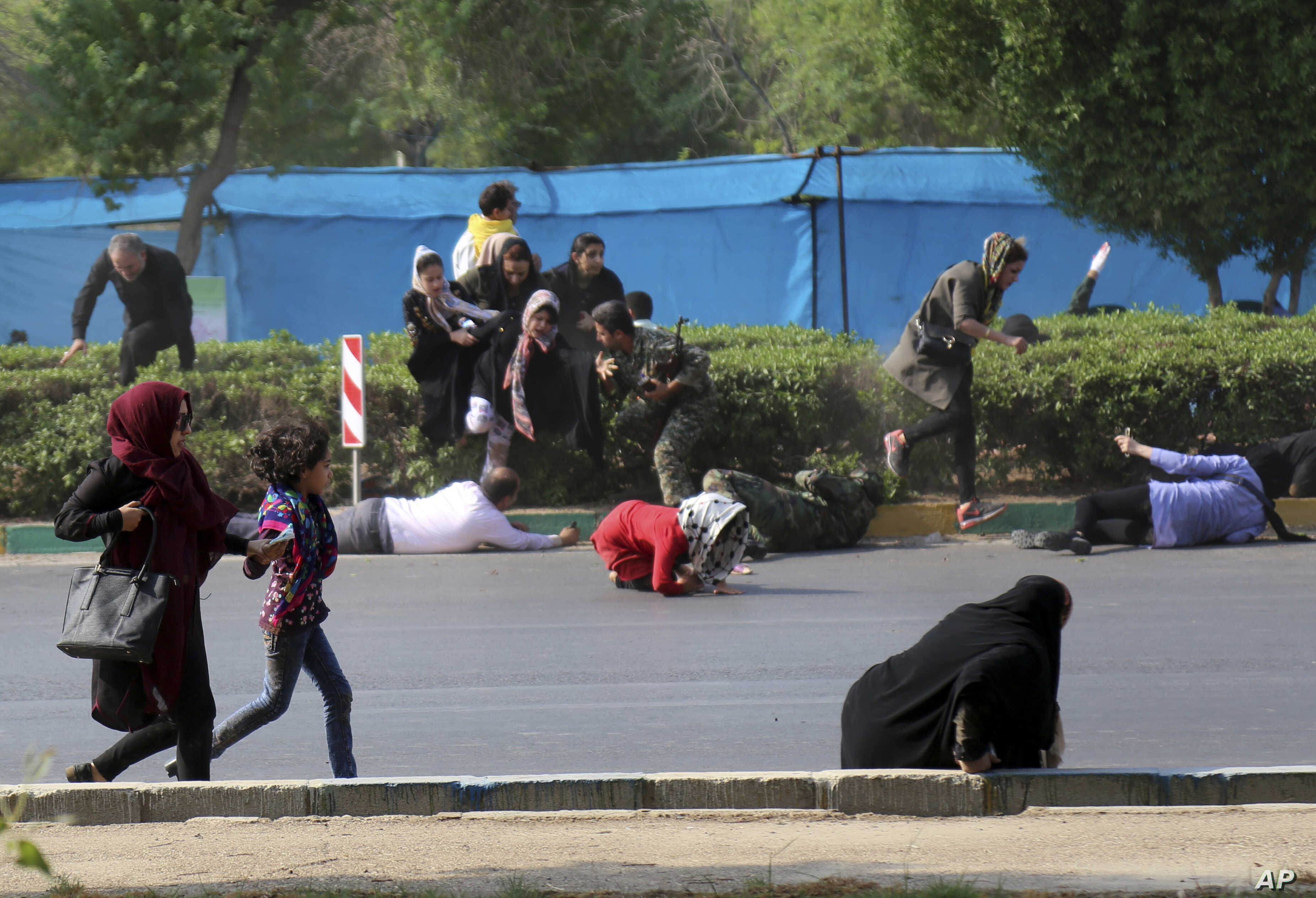 In this photo provided by Mehr News Agency, civilians try to take cover in a shooting attack during a military parade marking the 38th anniversary of Iraq's 1980 invasion of Iran, in the southwestern city of Ahvaz, Iran, Sept. 22, 2018.