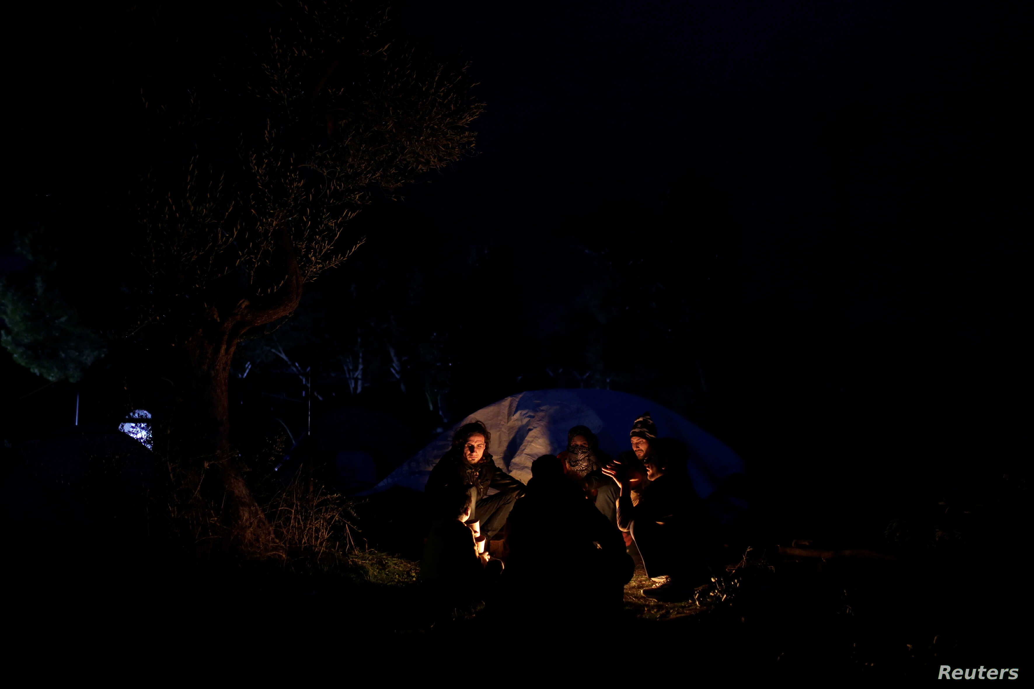 A Syrian family sits around a bonfire at a makeshift camp for refugees and migrants next to the Moria camp on the island of Lesbos, Greece, Nov. 30, 2017.