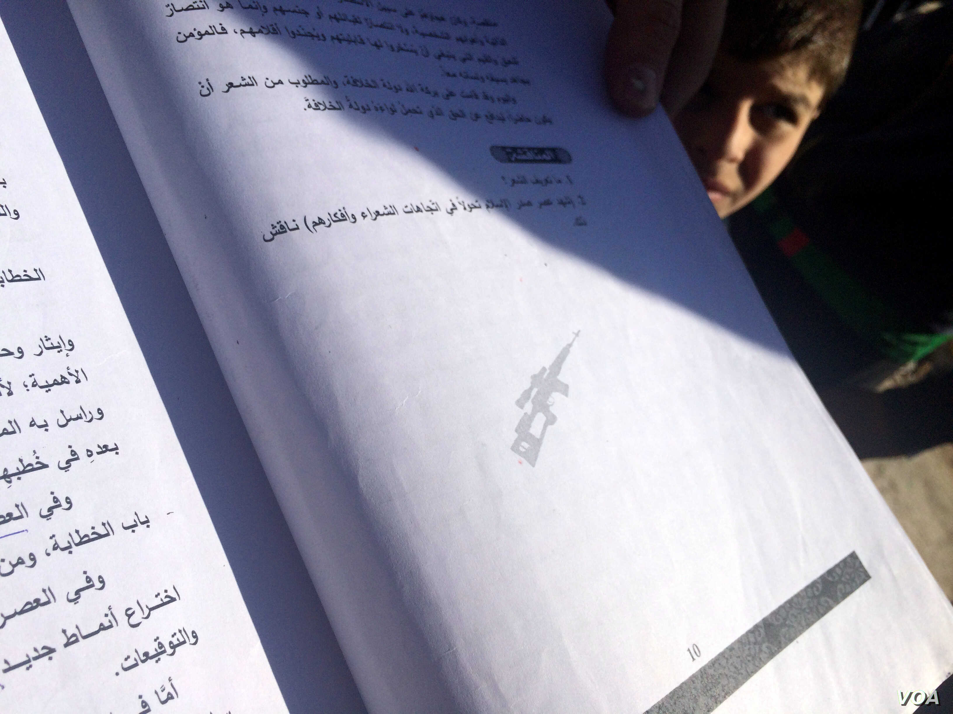 Teachers point out AK-47 logos and prayers for dead al-Qaida leaders on book pages in Mosul, Iraq, Nov. 23, 2016. (H. Murdock/VOA)
