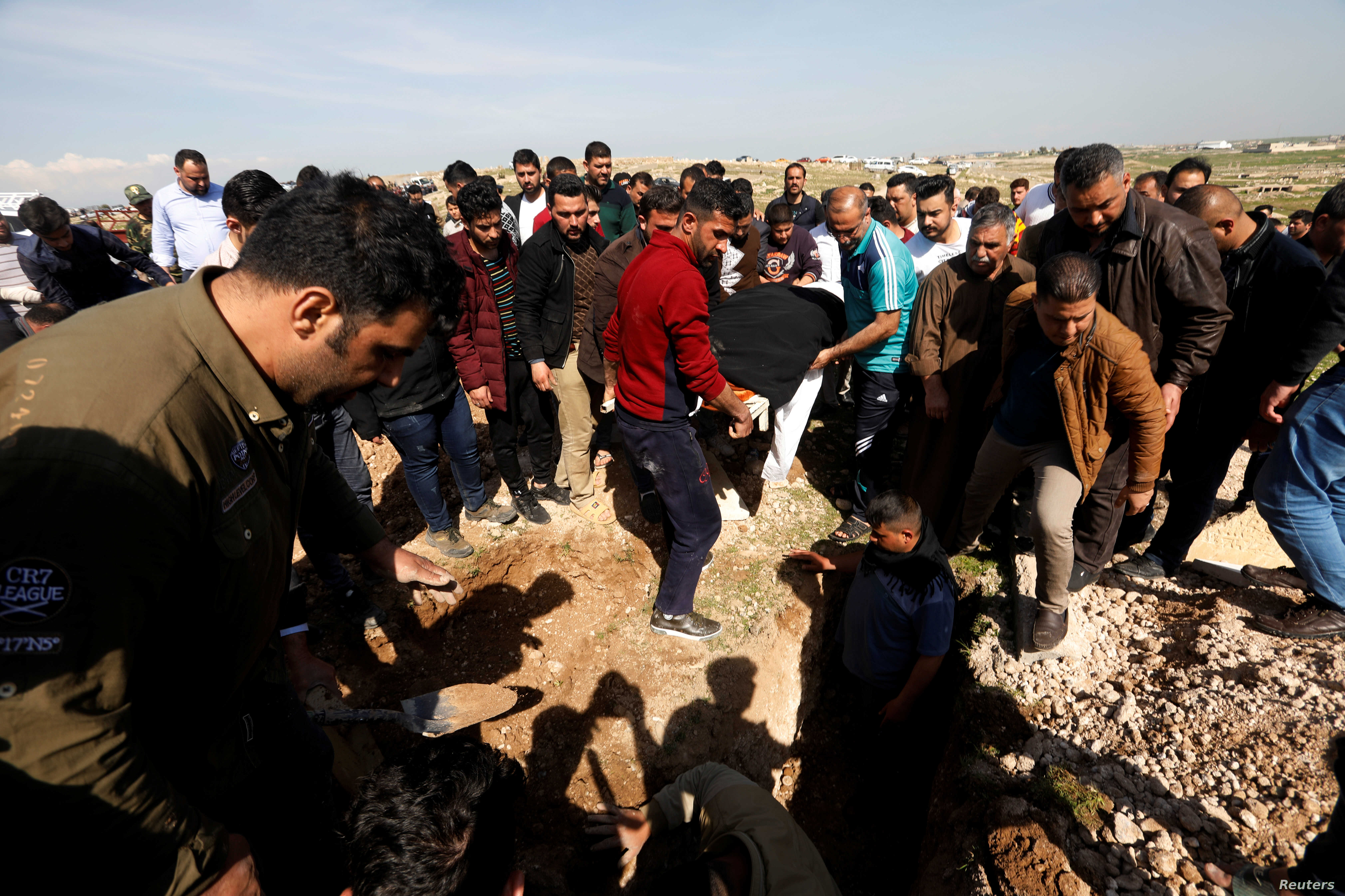 Mourners carry one of the victims who died after an overloaded ferry sank in Tigris river near Mosul, during his funeral at Mosul cemetery, Iraq, March 22, 2019.