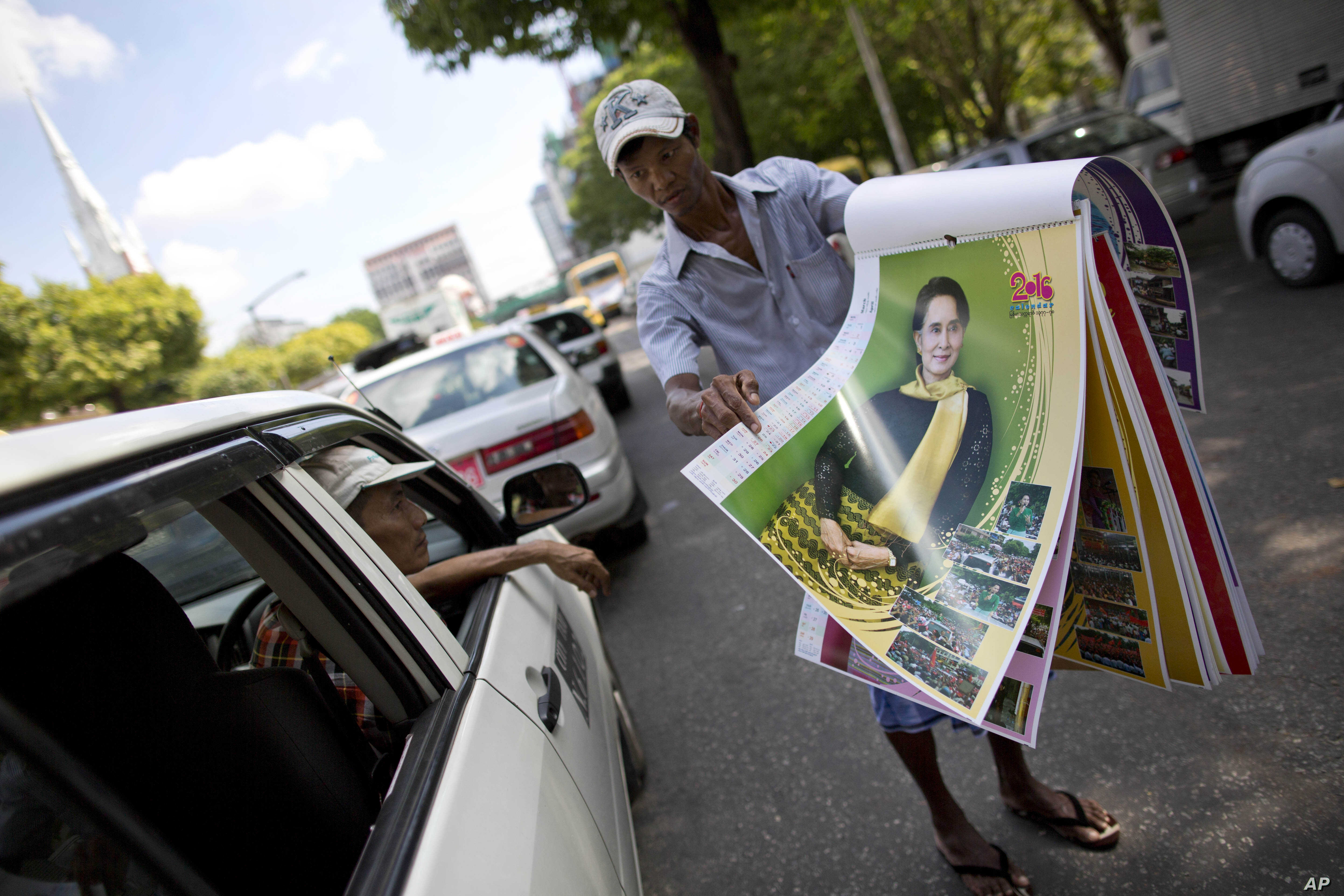 A street vender unfolds pages of a calendar featuring Myanmar's opposition leader Aung San Suu Kyi in a Yangon street, Myanmar, Nov. 12, 2015.